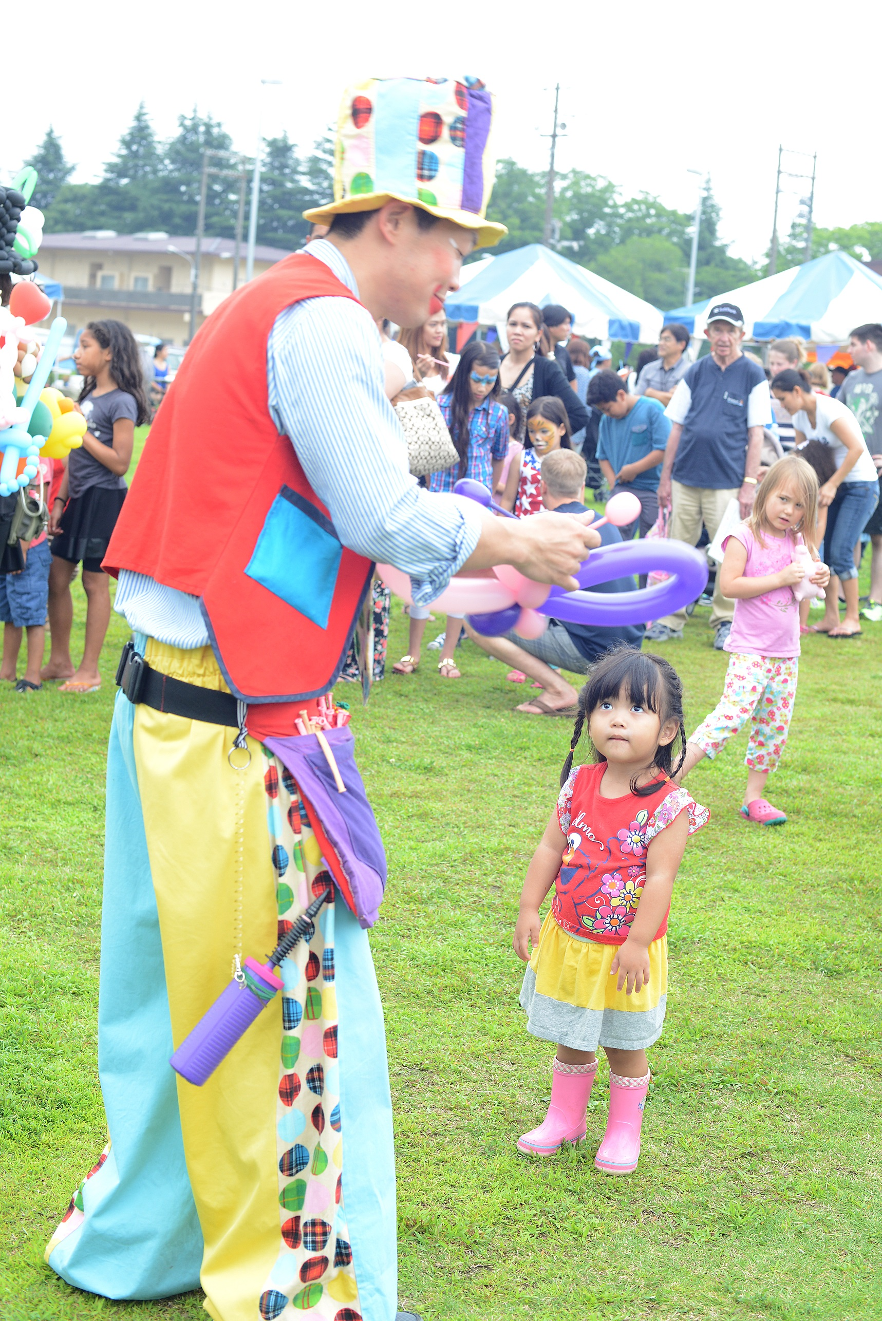 A clown shapes a pair of balloon wings for a child during Celebrate America at Yokota Air Base, Japan, July 2, 2015. Yokota residents gathered together to celebrate Independence Day with live music, food and fireworks. (U.S. Air Force photo by Airman 1st Class David C. Danford/Released)