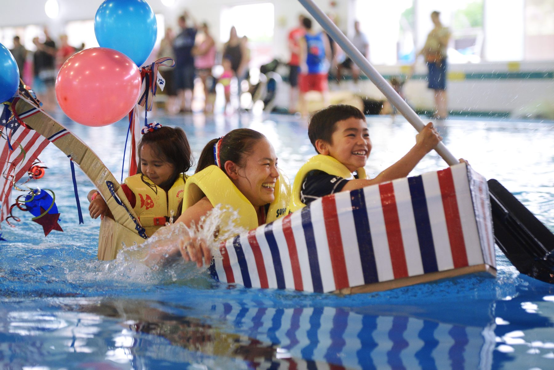 A family races to victory in the Leaky Kon Tiki race during Celebrate America at Yokota Air Base, Japan, July 2, 2015. The race, hosted by the 374th Force Support Squadron, was one of many events held during Celebrate America. (U.S. Air Force photo by Airman 1st Class Delano Scott/Released)