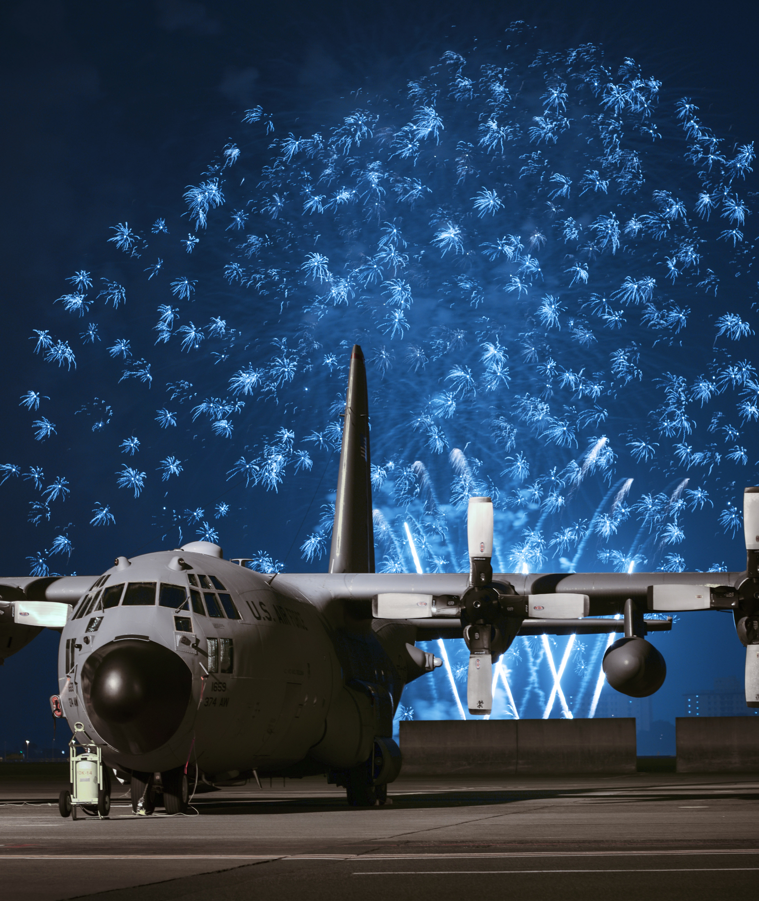 Fireworks explode behind a C-130 Hercules during Celebrate America, July 2, 2015, at Yokota Air Base, Japan. Celebrate America is an annual event that provides military members and their families the opportunity to enjoy games, food and bands before culminating in a fireworks display over the Yokota airfield to celebrate Independence Day. (U.S. Air Force photo by Airman 1st Class Delano Scott/Released)