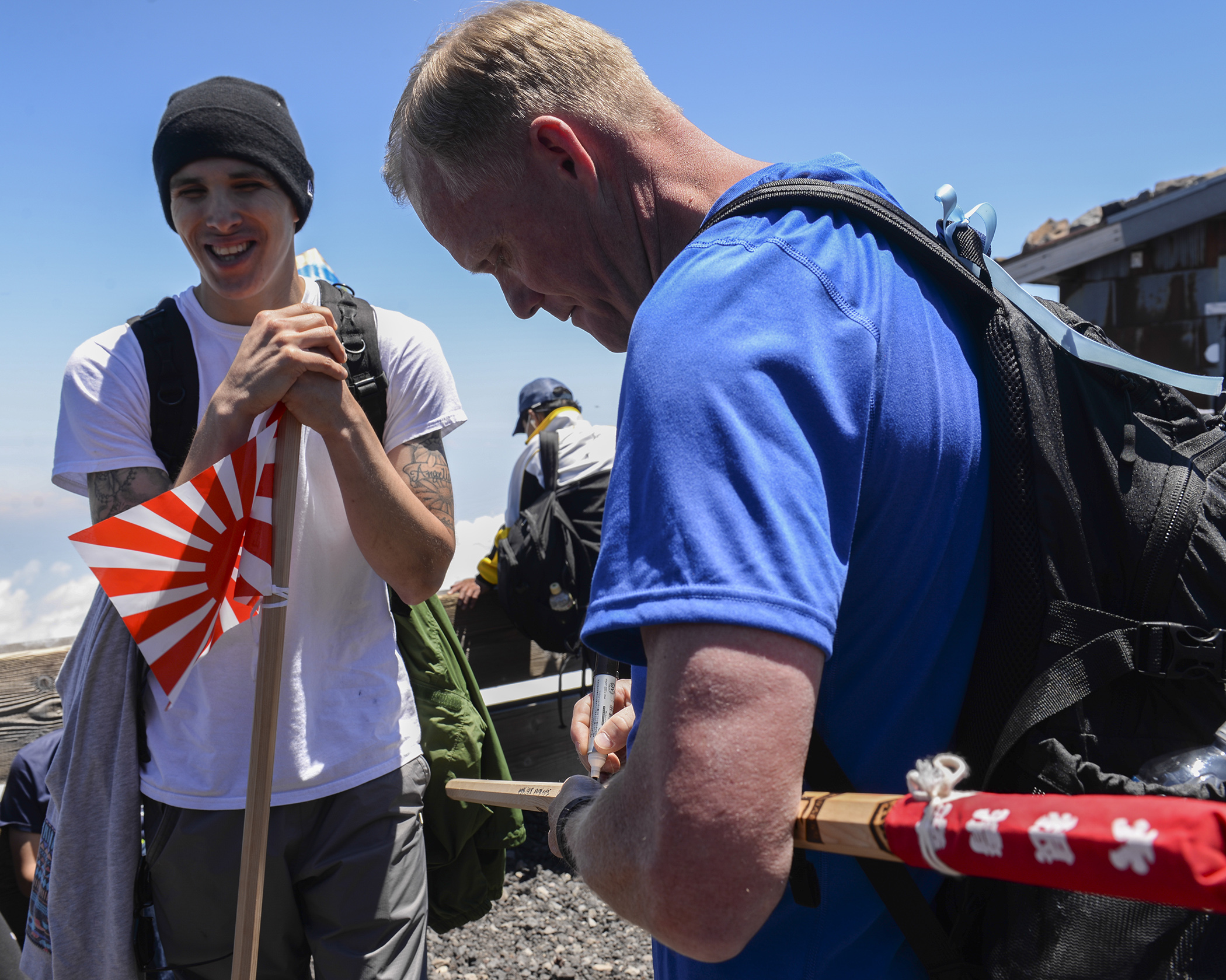 Chief Master Sergeant of the Air Force James A. Cody signs a walking stick for an Airman at the summit of Mount Fuji, Japan, July 11, 2015. During his trip to Japan, Cody extended an opportunity to 85 Yokota personnel to join him on a resiliency day trip to the summit of Mount Fuji. (U.S. Air Force photo by Airman 1st Class Elizabeth Baker/Released)
