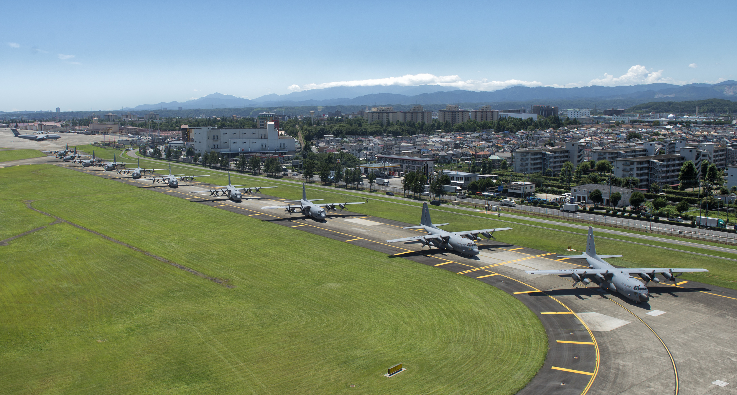 Ten C-130 Hercules aircraft taxi down a runway during a training exercise July 14, 2015, at Yokota Air Base, Japan. The exercise tested Yokota's ability to perform large-force employment and tactics. (U.S. Air Force photo by Airman 1st Class Delano Scott/Released)