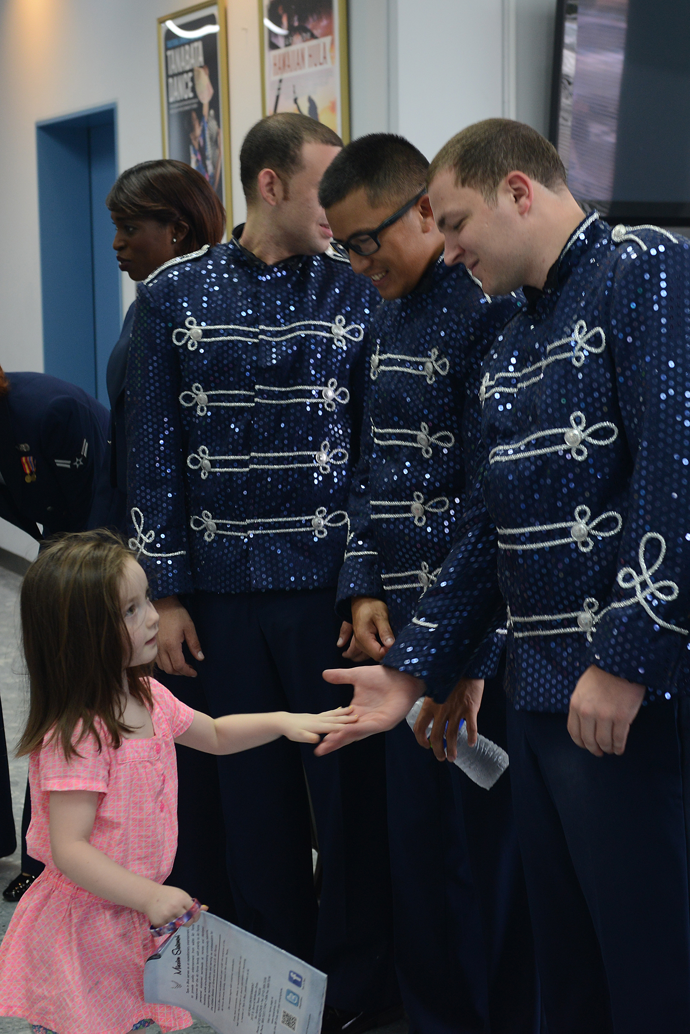 A child high-fives musicians after a Tops in Blue performance at Yokota Air Base, Japan, July 19, 2015. Tops in Blue promotes community relations, support recruiting efforts and serve as ambassadors for the U.S. and the Air Force when performing overseas. (U.S. Air Force photo by Airman 1st Class David C. Danford/Released)