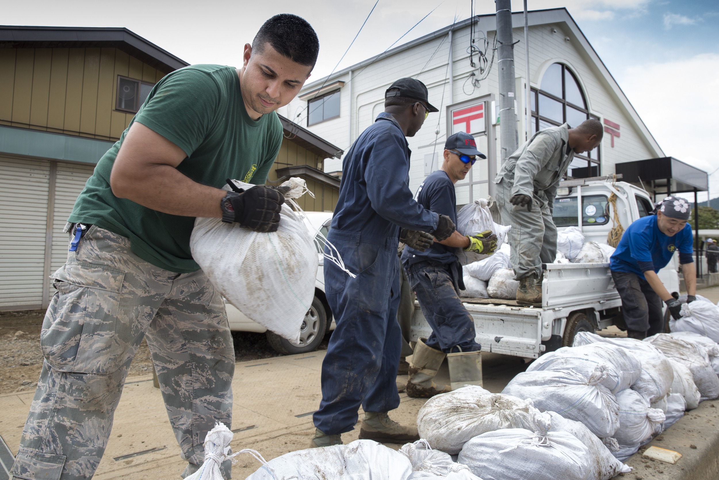 Volunteers from the 374th Civil Engineer Squadron establish an assembly line to download bags full of mud from a transport truck at Kanuma City, Tochigi Prefecture, Japan, Sept. 15, 2015. Sixty Airmen and civilians from the 374th CES volunteered to help at sites in the Kasono area in support of floods and landslides caused by the heavy rainfall associated with the post-tropical remnant of Tropical Storm Etau, which stalled over eastern Japan, dumping up to 17 inches of rain in 24 hours, from Sept. 10 to Sept. 11. (U.S. Air Force photo by Osakabe Yasuo/Released)