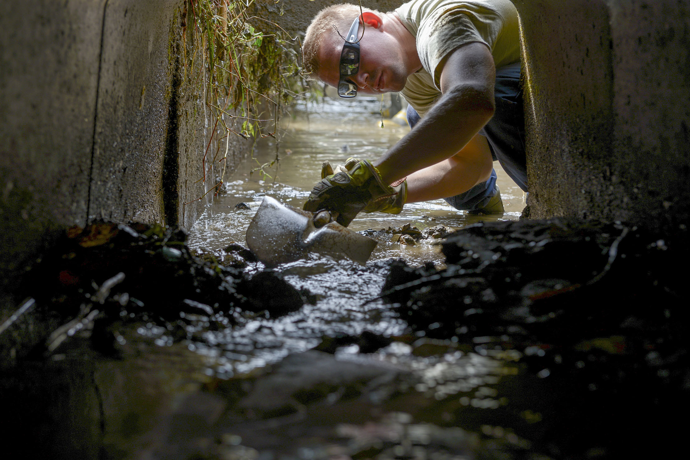 Airman 1st Class Thomas Smith, 374th Civil Engineer Squadron fire protection services, shovels mud from an irrigation system at Kanuma City, Tochigi prefecture, Japan, Sept. 15, 2015. Smith and other members of a large volunteer force from Yokota Air Base, ventured to Tochigi to assist the locals with mud removal, sand bagging and fixing what was broken during a recent flood and landslide. (U.S. Air Force photo by Staff Sgt. Cody H. Ramirez/Released)