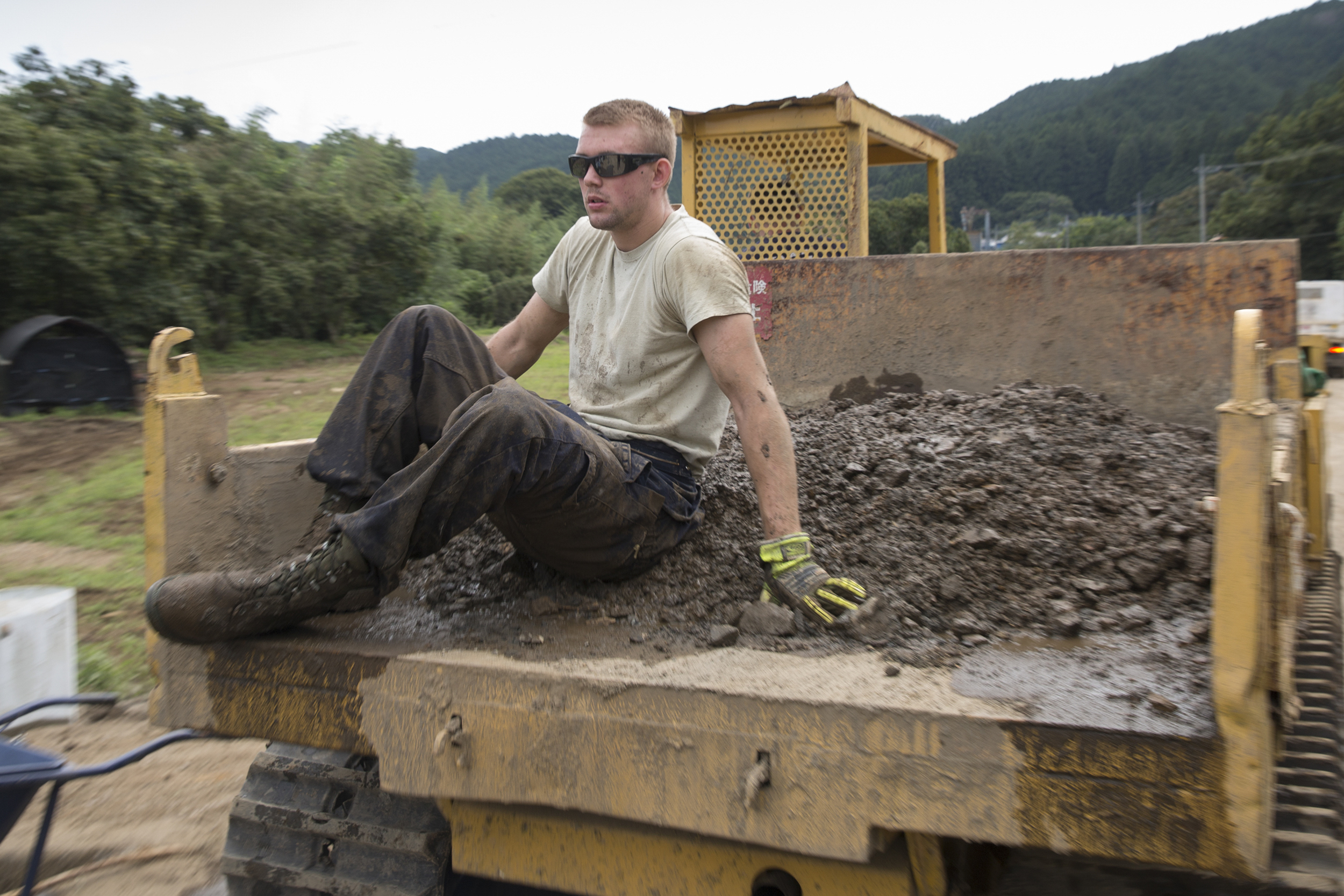 Airman 1st Class Thomas Smith, 374th Civil Engineer Squadron fire protection, rides in the back of a truck moving mudflow at Kanuma City, Tochigi Prefecture, Japan, Sept. 15, 2015. Sixty Airmen and civilians from the 374th CES volunteered to help at sites in the Kasono area in support of floods and landslides caused by the heavy rainfall associated with the post-tropical remnant of Tropical Storm Etau, which stalled over eastern Japan, dumping up to 17 inches of rain in 24 hours, from Sept. 10 to Sept. 11. (U.S. Air Force photo by Osakabe Yasuo/Released)