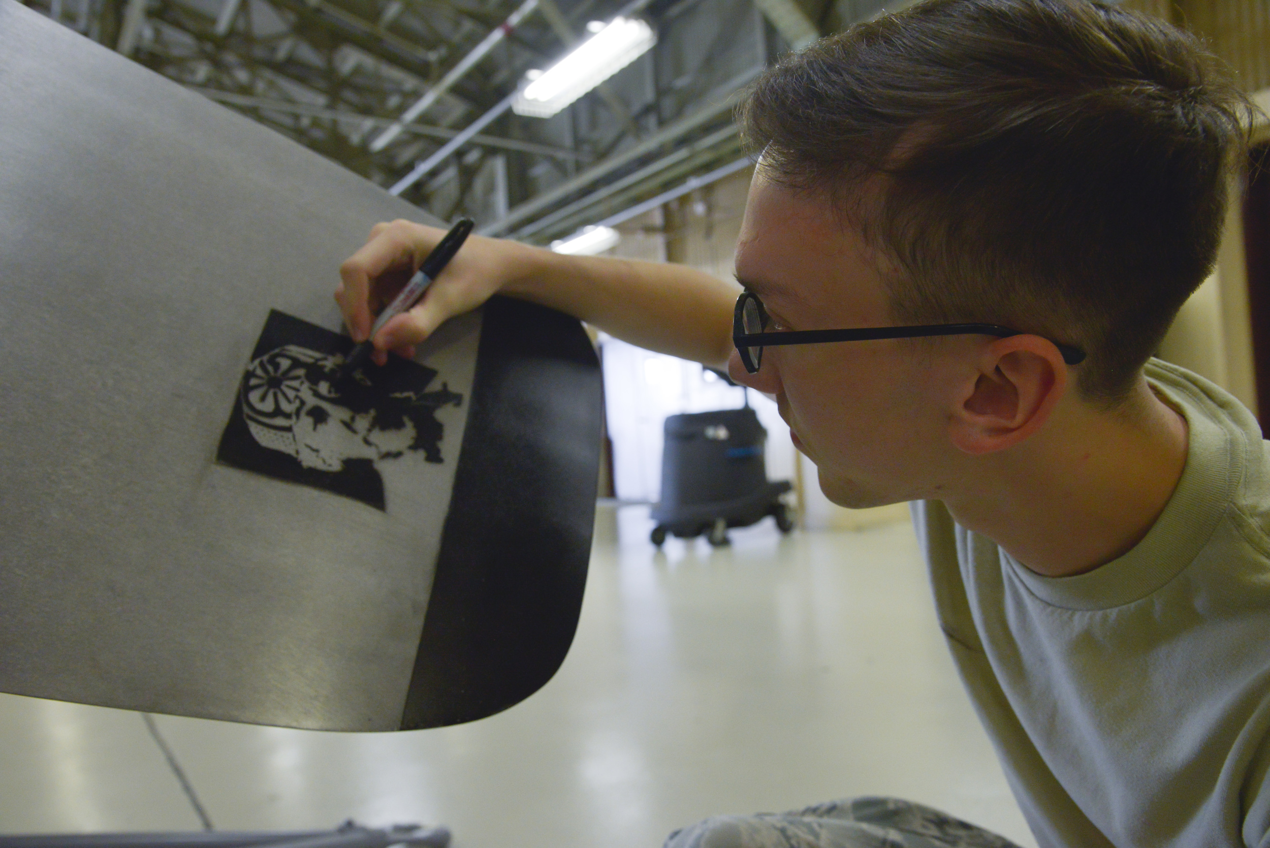 Airman 1st Class Kyle Cazier, 374th Maintenance Squadron propulsion flight aerospace propulsion apprentice, darkens part of a 'Mr. Miyagi' drawing on a propeller blade at Yokota Air Base, Japan, Sept. 23, 2015. The drawing is a reference point on the number three blade to ensure the number one blade is kept pointing up, preventing hydraulic fluid leaks. (U.S. Air Force photo by Senior Airman David Owsianka/Released)