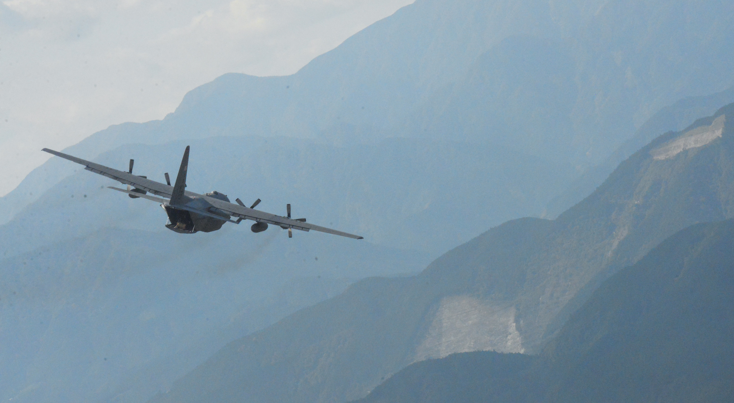 A C-130 Hercules flies over a mountainous region of Japan, Oct. 14, 2015. Performing regular in-flight operations gives all related operations personnel real -world experience to stay prepared for contingency situations. (U.S. Air Force photo by Airman 1st Class Elizabeth Baker/Released)