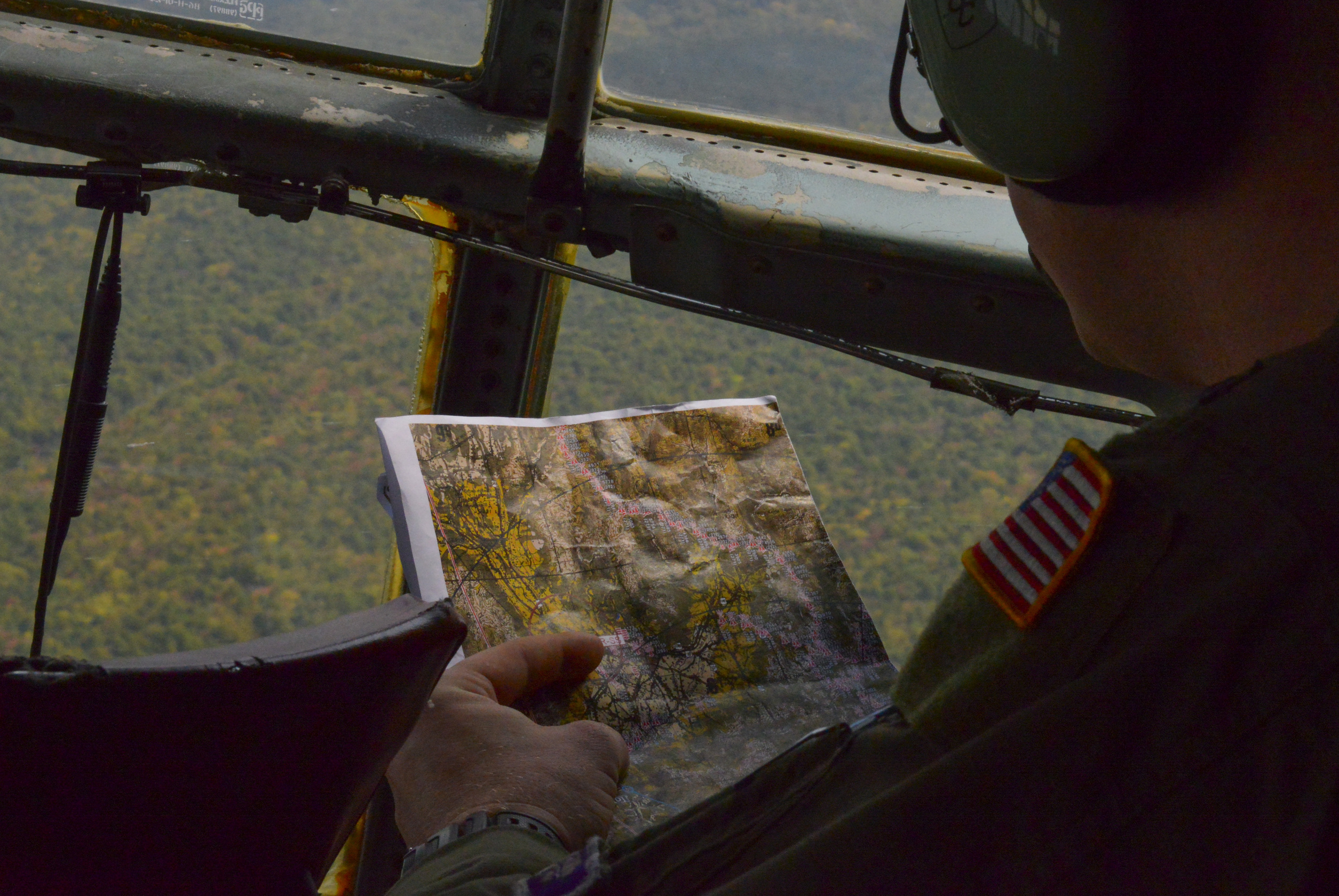 Capt. Byron Luckett, 36th Airlift Squadron C-130 Hercules copilot, identifies landmarks while flying over the mountains of Japan, Oct. 14, 2015. Air crew regularly practice realistic scenarios to make sure they are ready to perform Yokota's airlift mission at all times. (U.S. Air Force photo by Airman 1st Class Elizabeth Baker/Released)