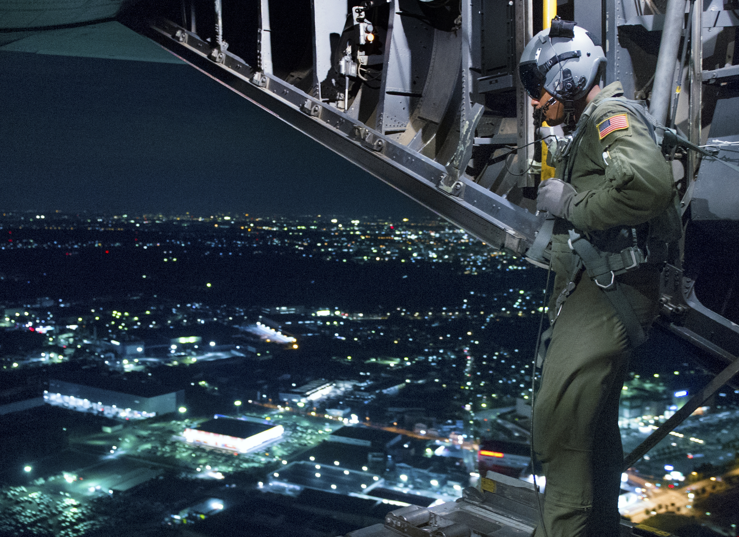 Senior Airman Gary Cole, 36th Airlift Squadron loadmaster, surveys a drop zone at Yokota Air Base, Japan, Oct. 14, 2015. The C-130 Hercules crew performed simulated drops and several landings and takeoffs all while using night vision goggles. (U.S. Air Force photo by Airman 1st Class Delano Scott/Released)