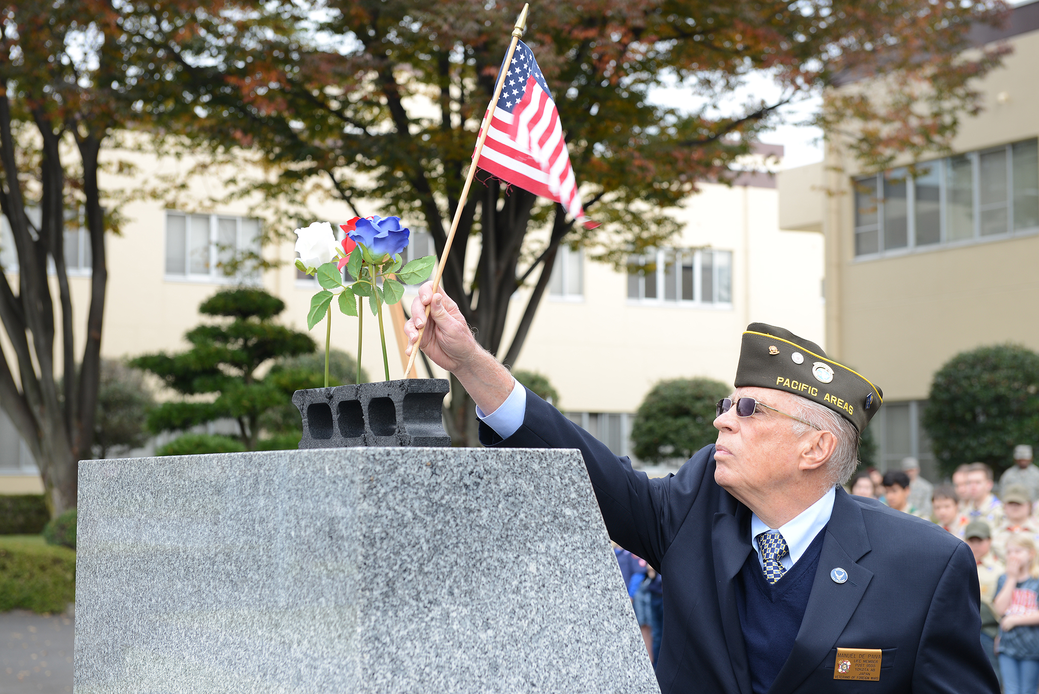 A member of the Veterans of Foreign Wars places an American flag on a monument during the three flower ceremony at Yokota Air Base, Japan, Nov. 11, 2015. The three flowers each have a different meaning: The red rose represents those who have died in defense of their country, the white celebrates future service members and the blue immortalizes the deeds of Soldiers, Sailors, Airmen and Marines. (U.S. Air Force photo by Senior Airman David C. Danford/Released)
