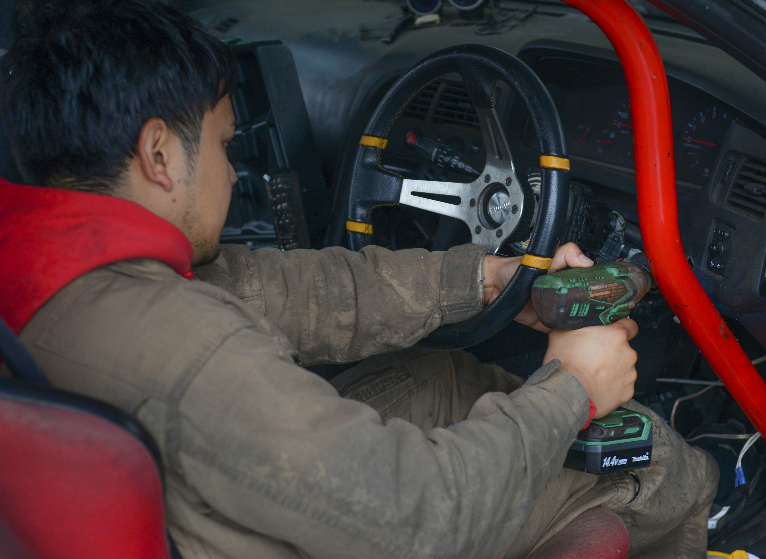 Angelo Manalastes drills a hole for the starter switch in his drift car at Ebisu Circuit, Japan, Nov. 14, 2015. Manalastes and a group of Yokota Airman spent two days at the fall drift festival at Ebisu, an event which attracts participants from around the world to drift. (U.S. Air Force photo by Airman 1st Class Elizabeth Baker/Released))