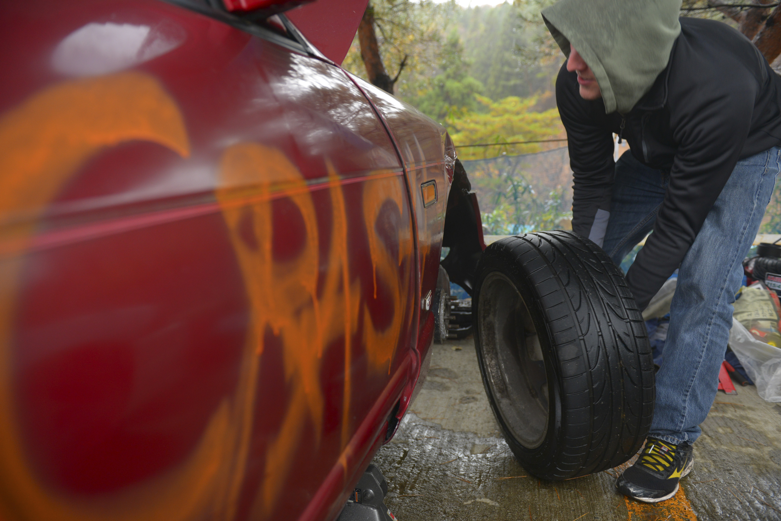 Airman 1st Class Hudson McCormick, 374th Maintenance Squadron hydraulics technician, changes the tire on a drift car at Ebisu Circuit, Japan, Nov. 14, 2015. McCormick and his friends spent many hours repairing the cars between stints on the track, time that was also used for socializing and meeting new people. (U.S. Air Force photo by Airman 1st Class Elizabeth Baker/Released)