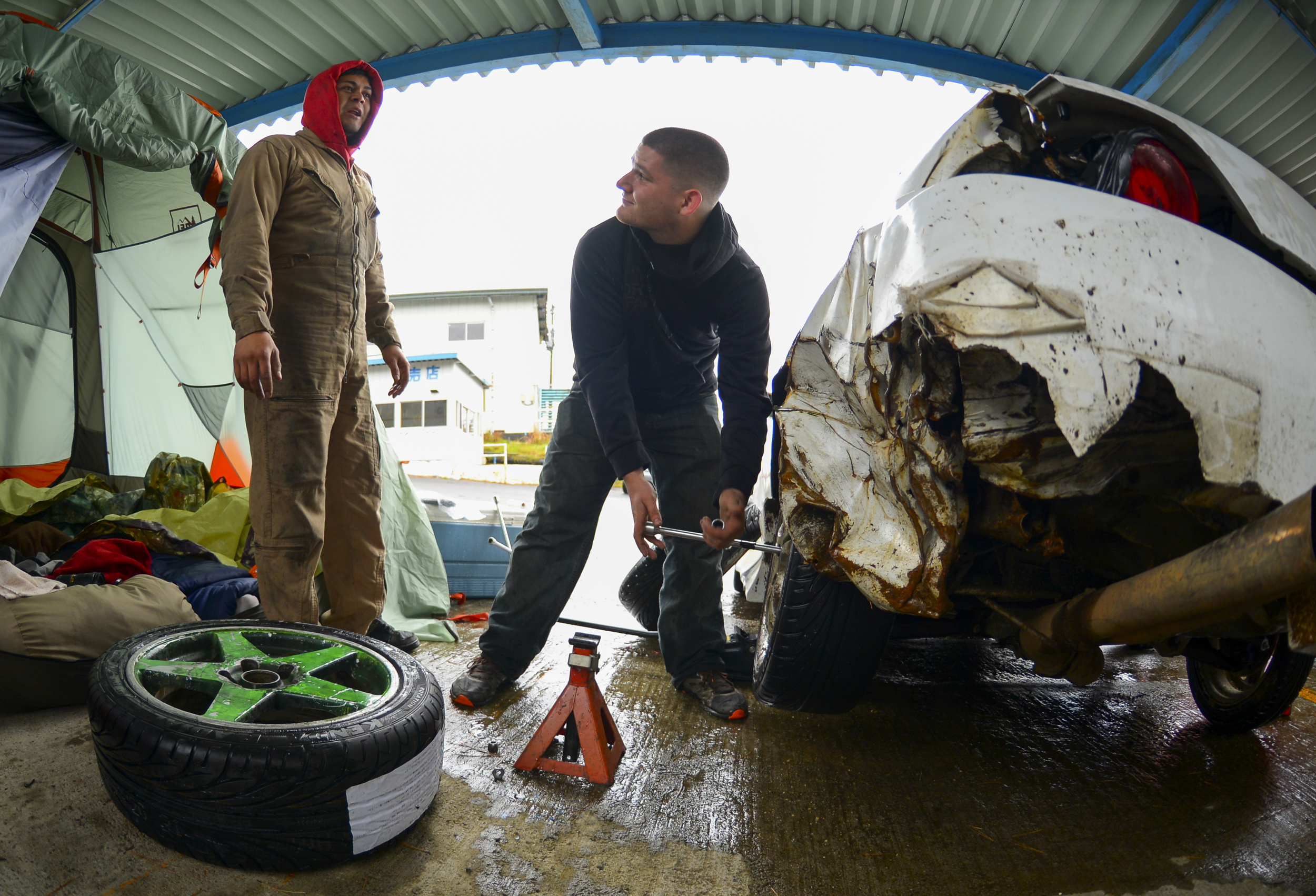Senior Airman Joseph Galloway, 730th Air Mobility Squadron jet propulsion technician, talks to Angelo Manalastes, a drift driver, while changing the tire on his drift car at Ebisu Circuit, Japan, Nov. 14, 2015. Drifting often burns tires down so quickly that they have to be changed at least twice a day, and causes such extensive damage that the cars cannot be legally driven outside the race track. (U.S. Air Force photo by Airman 1st Class Elizabeth Baker/Released)