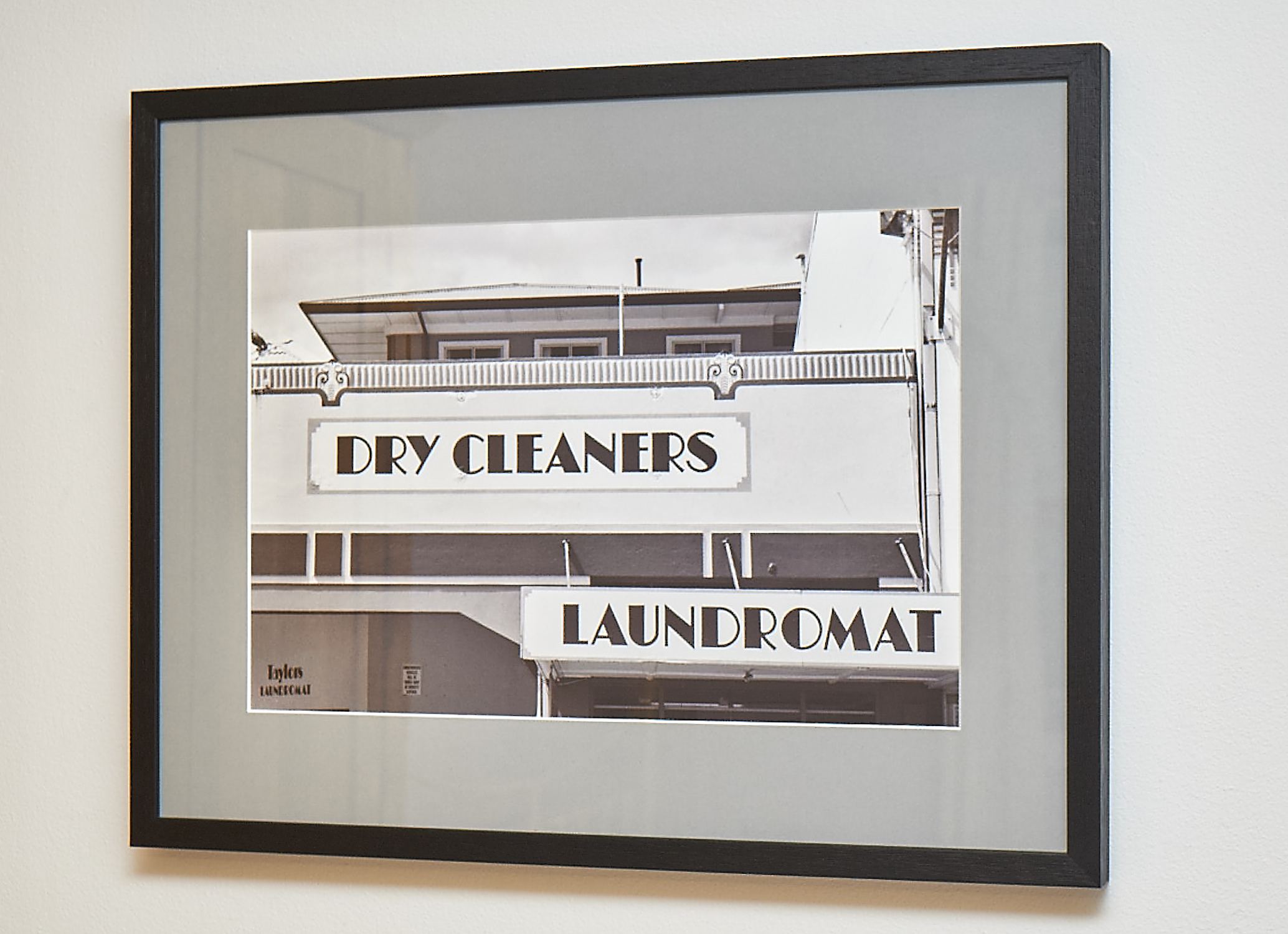 """Dry Cleaners   This was shot in the New Zealand town of Napier. Following earthquake devastation in 1931, the town was rebuilt in the mode of the day, Art Deco. A fascinating place.  Shot on black & white film, and framed in a black frame with grey border.   Frame Size approx. 24 x 19""""    COST £40.00"""