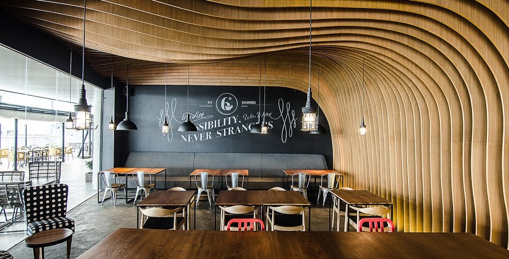 OOZN DESIGN  has created cavernous cafe in Jakarta -  Six Degrees Cafe using undulating timber slats around the walls and ceiling to make a memorable and cosy cafe.