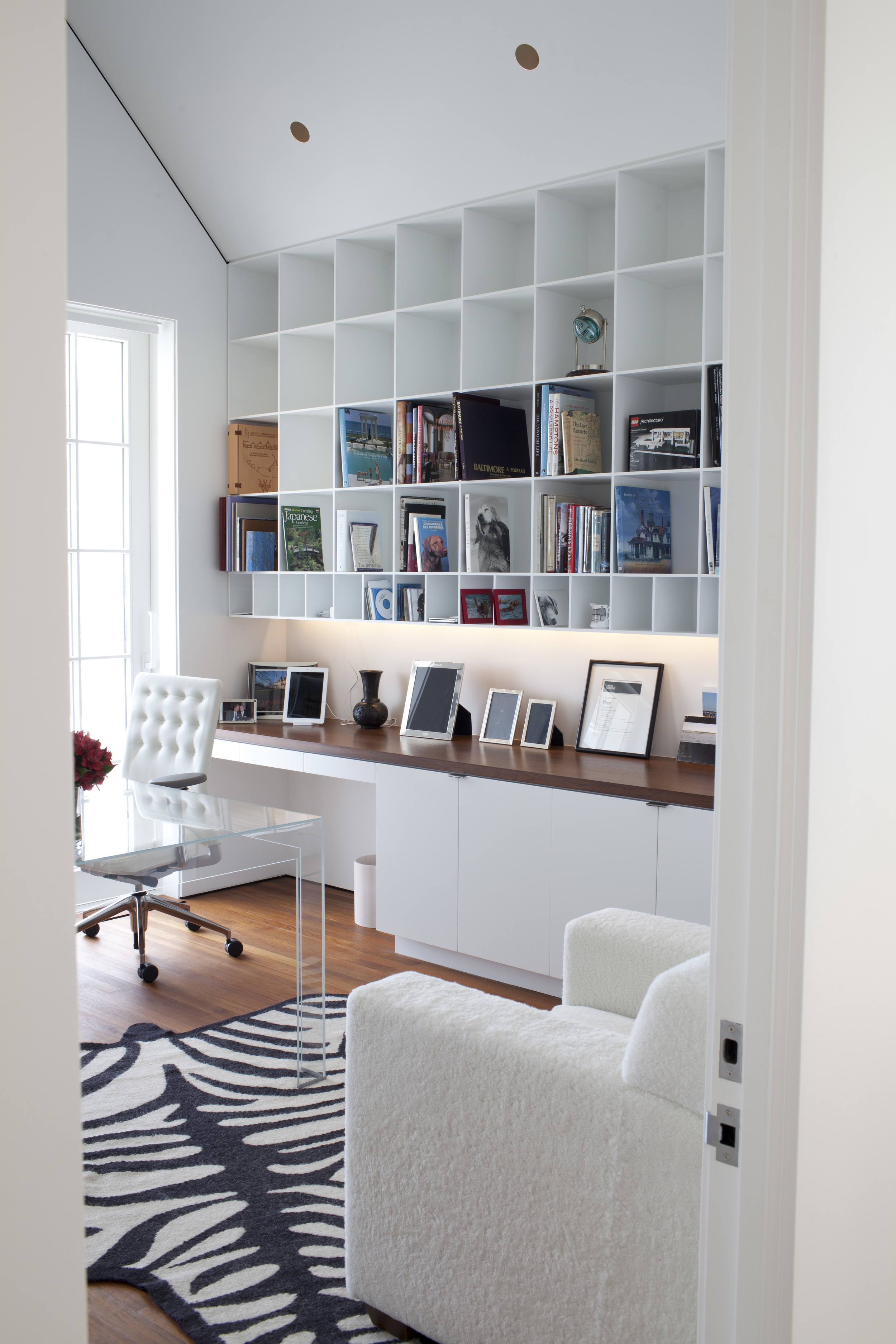 Bookcases over a desk and hidden lights.