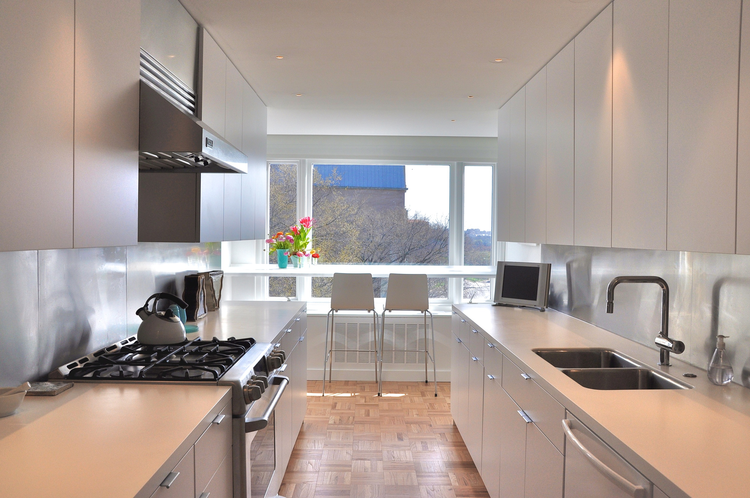 A cool, minimalist kitchen in an apartment in Washington and translucent counter over looking the avenue.