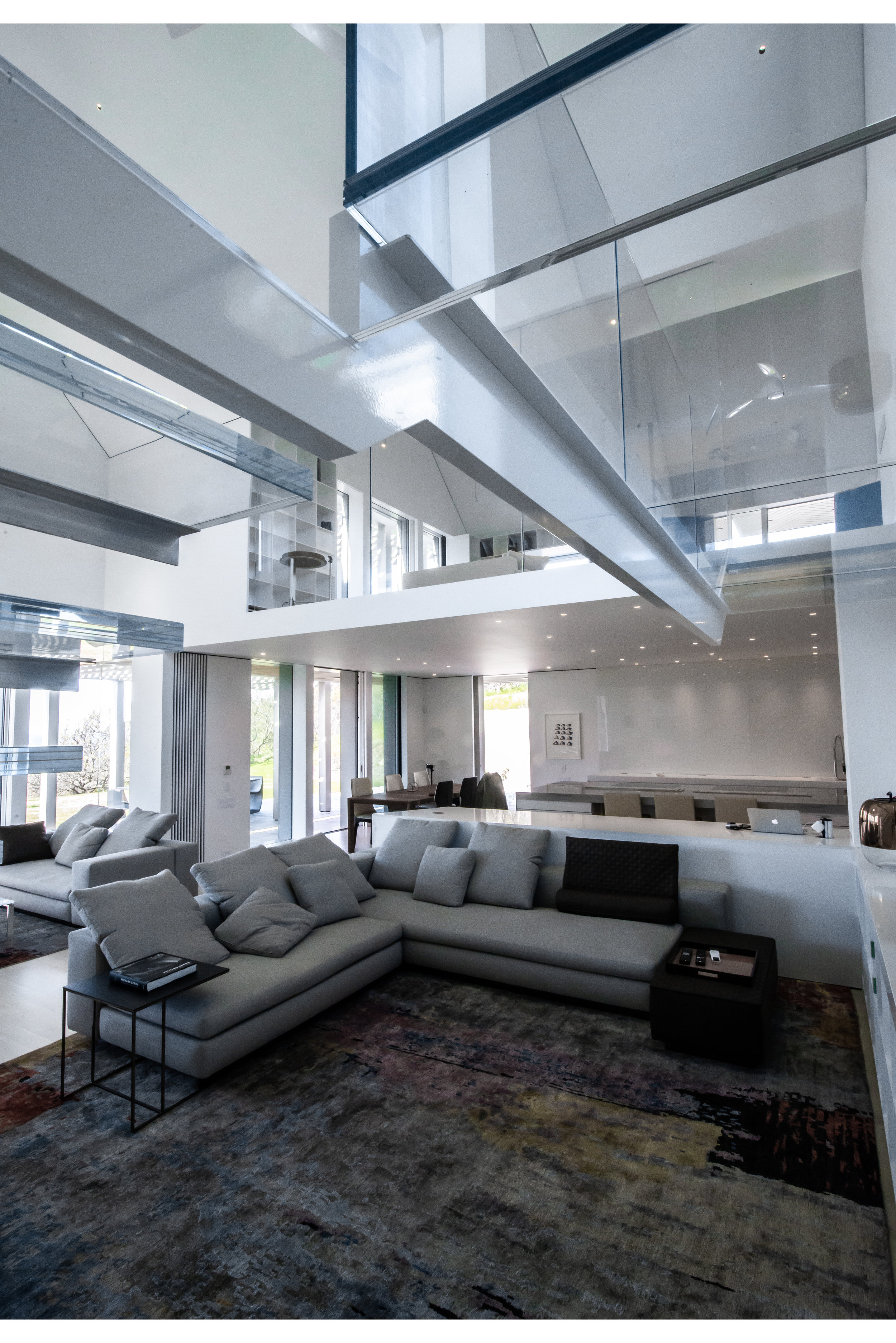 A glass bridge and glass staircase with exposed steel beams.