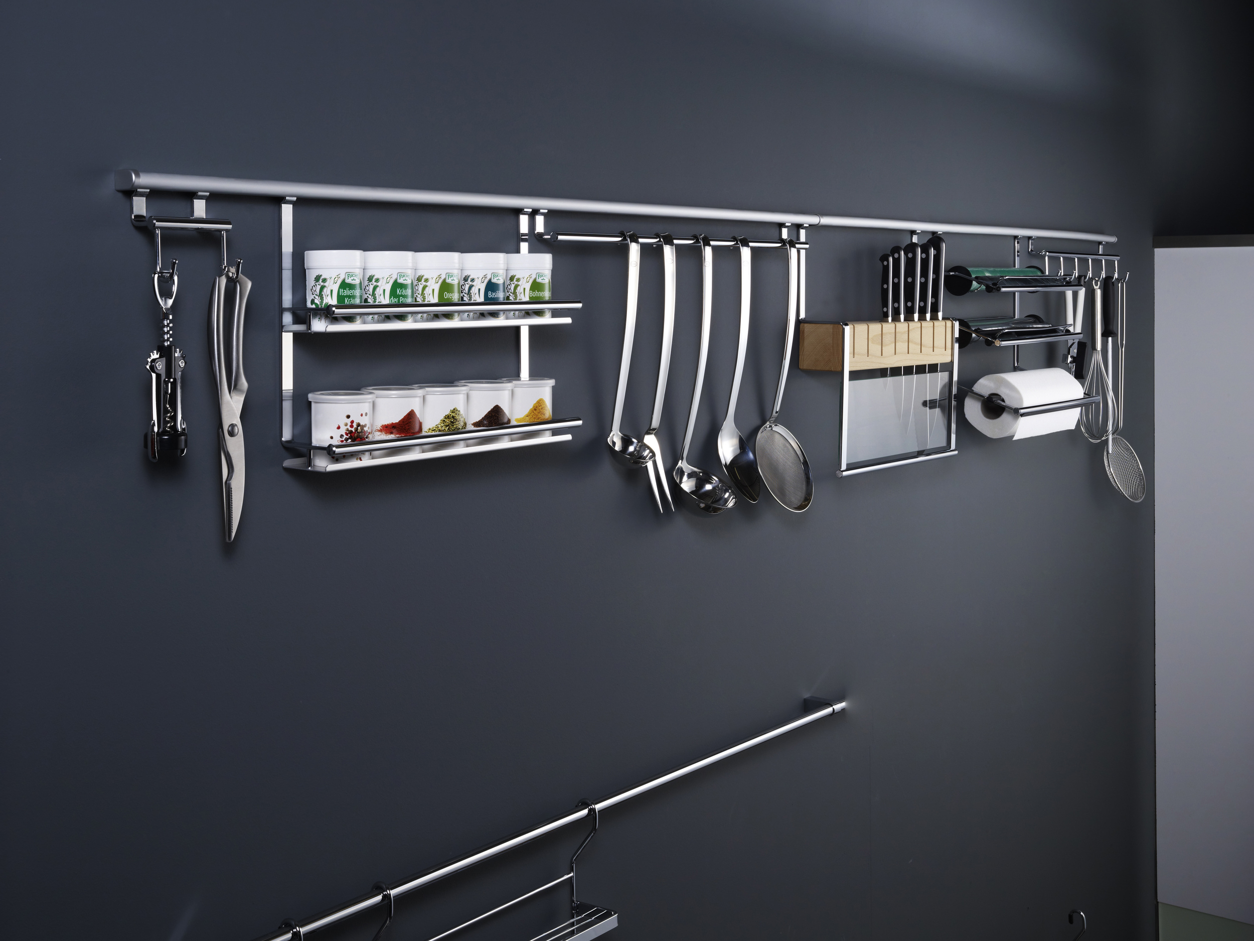 """Design creates order. Or perhaps, in the case of LINERO 2000 railing systems, order creates design. This full line of innovative storage accessories was created for the cook who prefers to keep every kitchen necessity close at hand.From our most popular cook book holder...to whisks, knives and small appliances. Even oils and spices. An assortment ofstylish accessories takes the LINERO 2000 from """"practical"""" to """"beautiful.""""  Ordinarily, you might assume it's necessary to open cabinets and drawers to find the kitchen tools you need. With a BACKSPLASH SYSTEM from Kesseböhmer, cooking utensils and more are in plain sight and right at hand. Choose from a huge selection. Sturdy mounting rails keep a low profile against walls and concealed connections add streamlined style."""