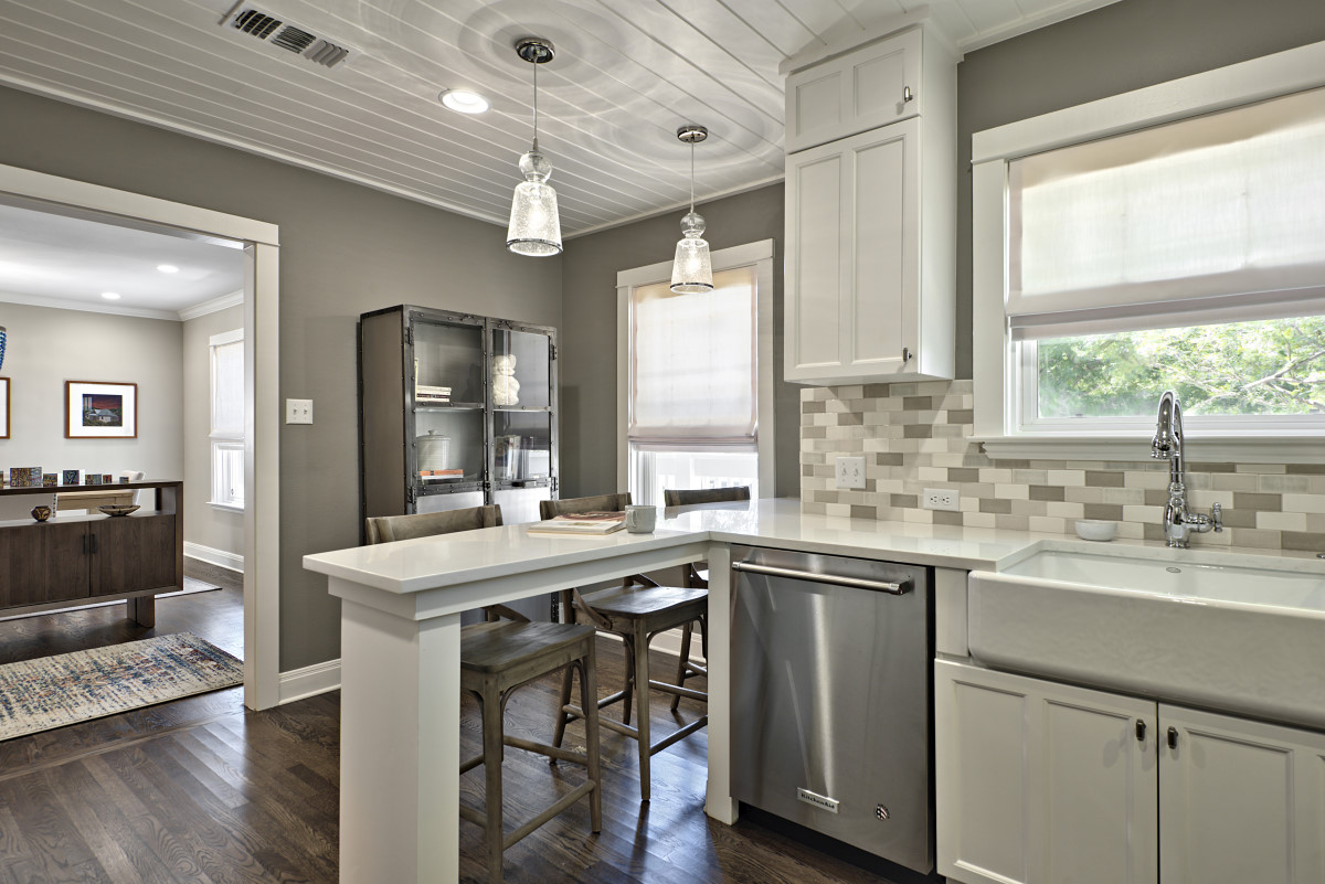 To create a practicality and generate the right mood, kitchen clutter was drastically reduced with a smart pantry that houses smaller appliances, and a custom-designed peninsula was created for convenient built-in seating.