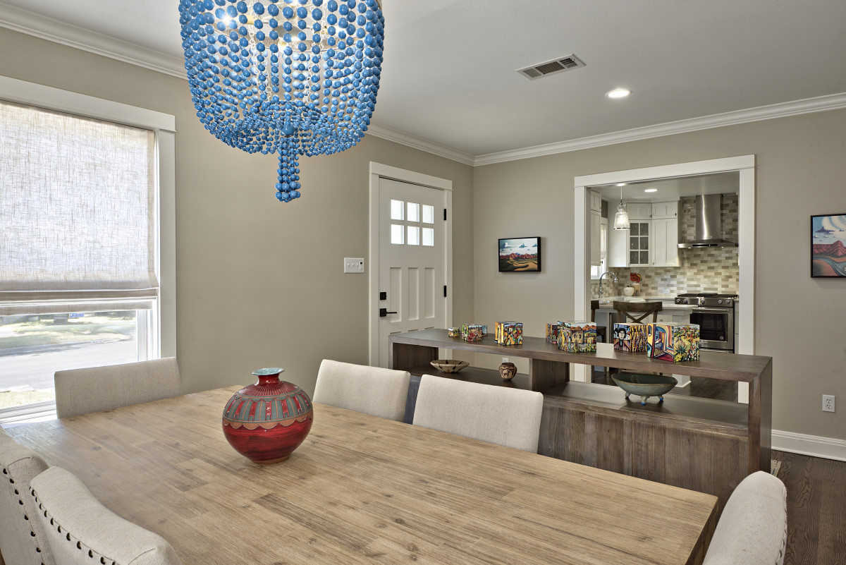 The front living space was transformed to an entry way and dining area, separated by a two-sided console. This new, airy floor plan along with an open entryway to the kitchen, provides the perfect scenario for welcoming and entertaining guests. The mood of each room was lifted with new lighting throughout; including a whimsical blue beaded chandelier over the dining table (seen here), practical (yet beautiful) task lighting under areas like kitchen cabinets, and broader, clean recessed lighting that gives a sense of daylight throughout the space.