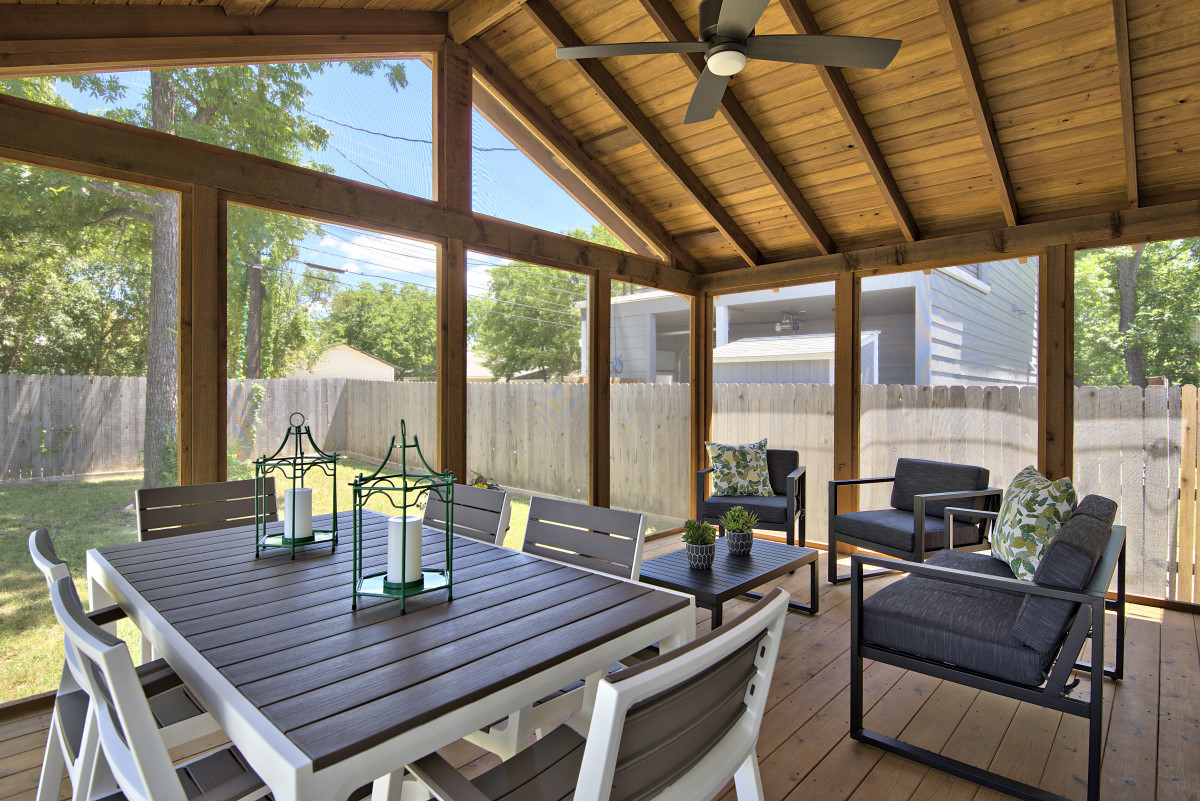 New furnishings for the existing screened-in porch add a touch of modern that sets off the rustic feel of the raw wood structure. Furniture placement allows for easy conversations and casual outdoor dining, while the nature inspired accessories pull the outside in.