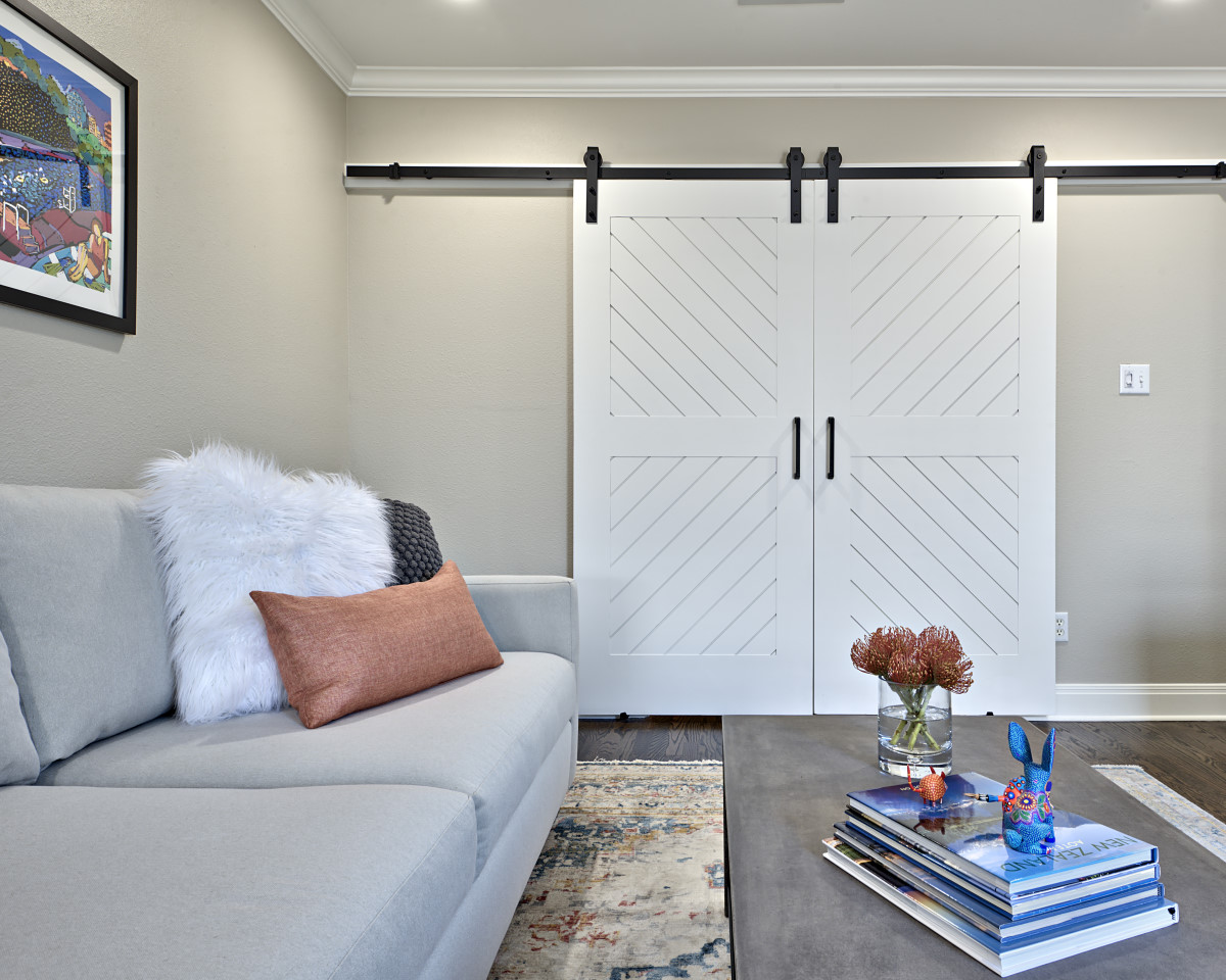 The former dining room was transformed into a family room. Custom designed barn doors allow the space to be open, in the case of entertaining, or closed to create a cozy, more intimate space for quality family time.