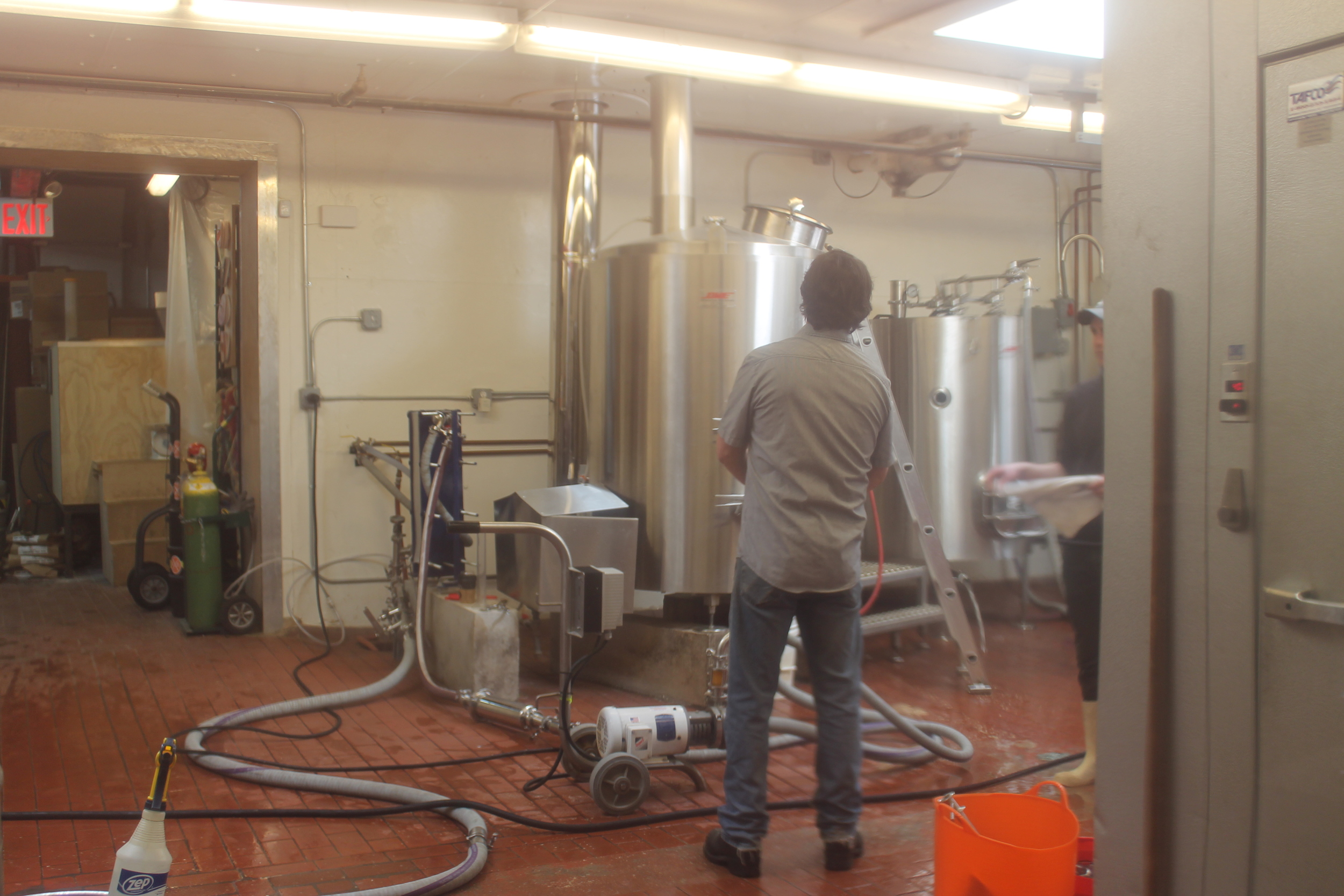 A view of John from the window in the door separating the brewery from the tasting room. Judging from the hoses, we're transferring the beer to the fermenter before pitching the yeast.
