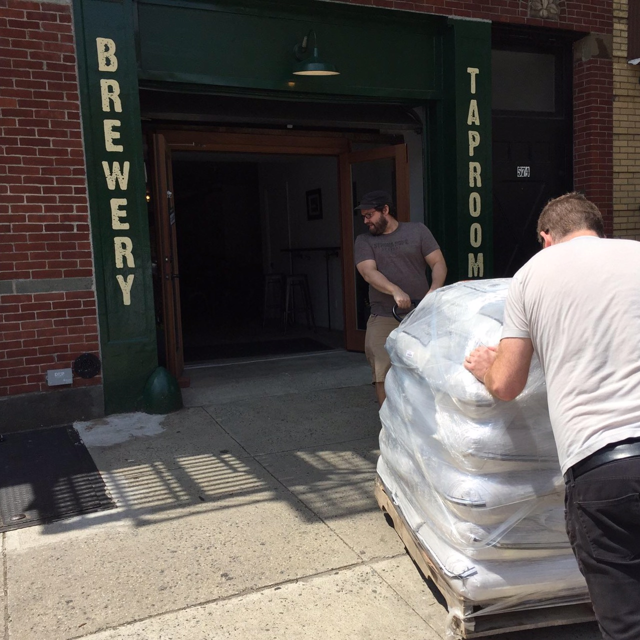 Jason Sahler (L.) and Eric Kimball (R.) intake an order of NY State grain during brew day. ( image courtesy of Mary Kimball )