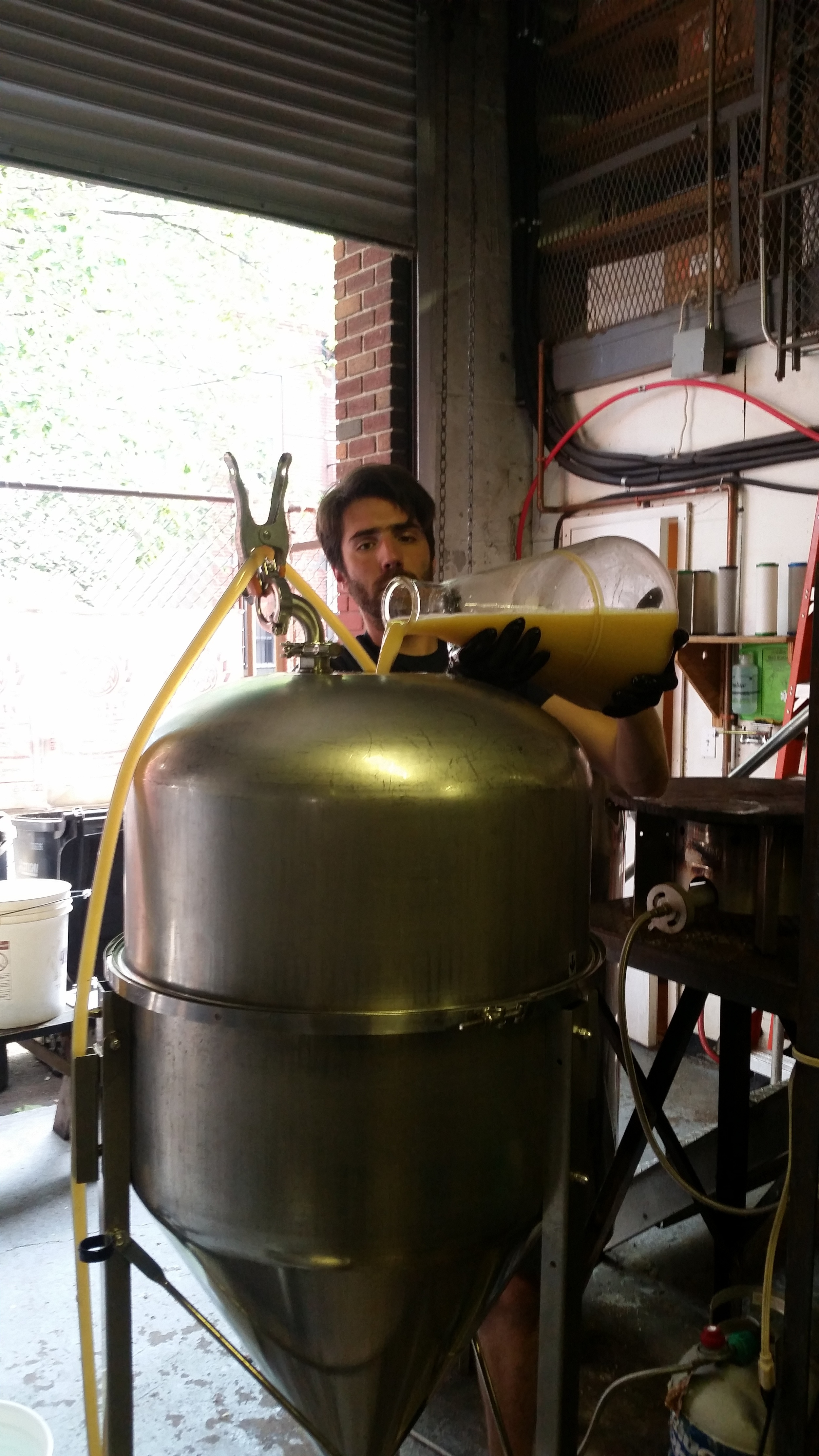 Folksbier Director of Brewery Operations, Joe Watts inoculating the wort with yeast.
