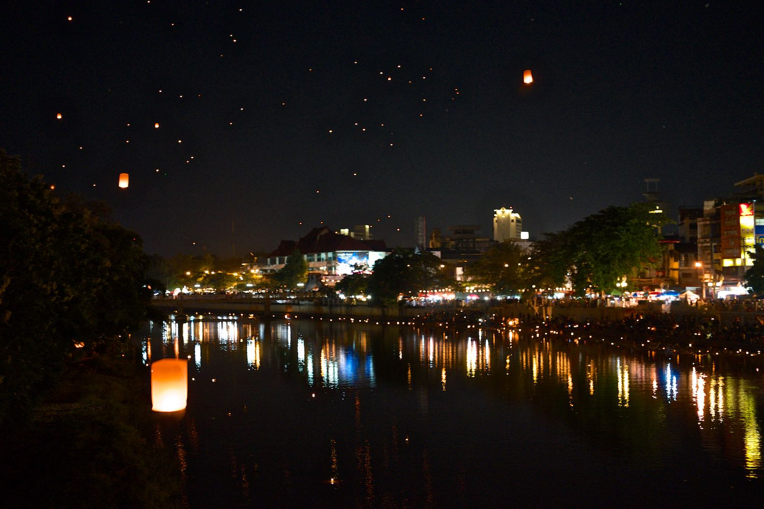 The river is lit up with Krathongs and the sky is filled with paper lanterns.