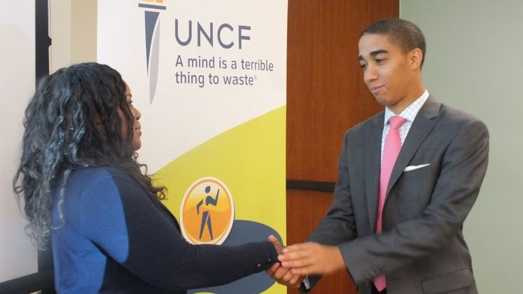 President, Dominique Jordan, shaking hands with Edison on behalf of their UNCF Walk For Education.  Marliss Gordon (left), president of SCE's Networkers Employee Resource Group, thanks Dominique Jordan for helping to promote this year's Walk for Education. Dominque is a past winner of UNCF's Gates Millennium Scholarship.