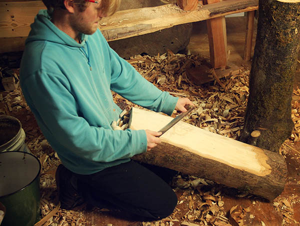 Shaving the bark off one side of the ash log with a drawknife.