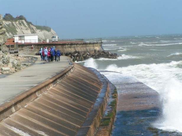 Photo of a hard seawall with ocean waves.