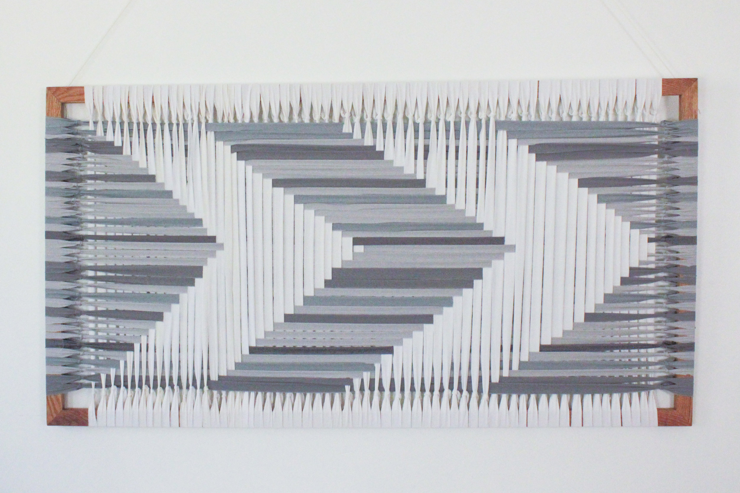 varied grays and white arrows woven on a frame by Jamie Tubbs.