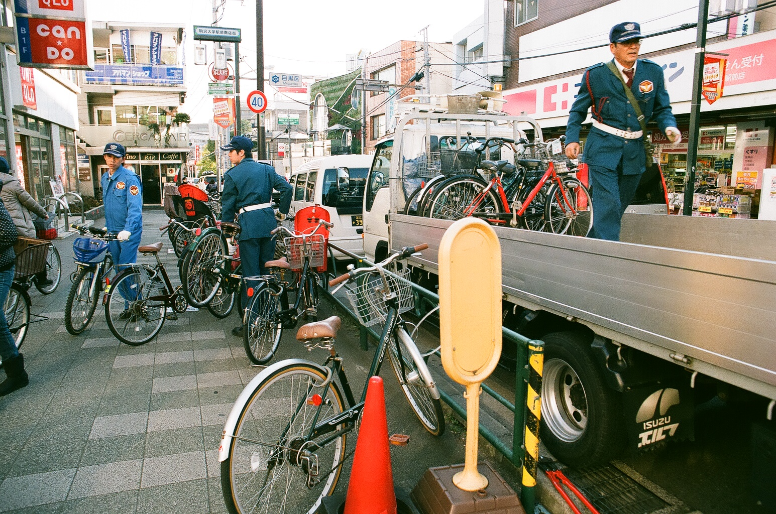 """No bikes are ever locked in Japan. These police officers are actually towing bikes that violated the """"no evening parking"""" multiple times. As soon as they left the this sidewalk was filled with more bikes!"""