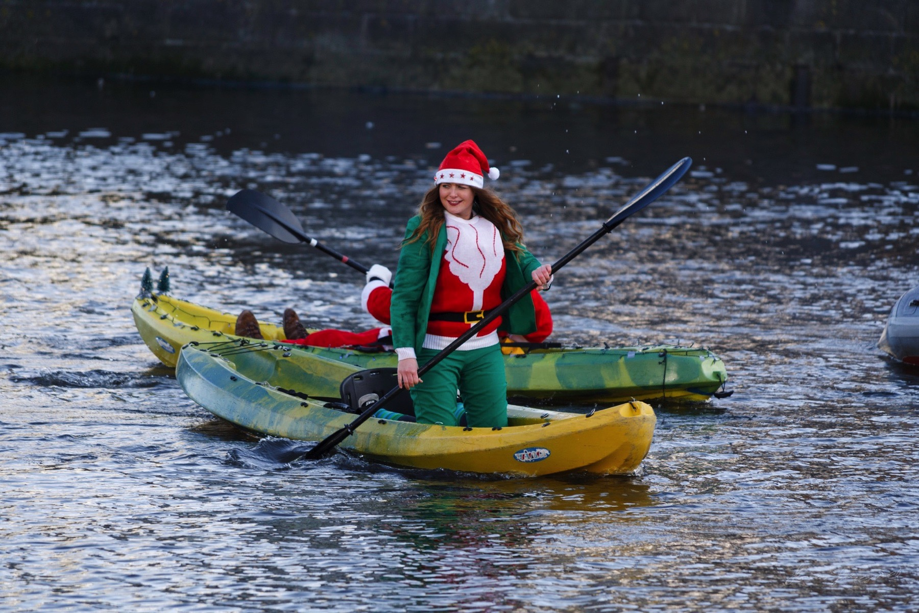 Woman dressed as a Christmas Elf on a kayak in the Liffey
