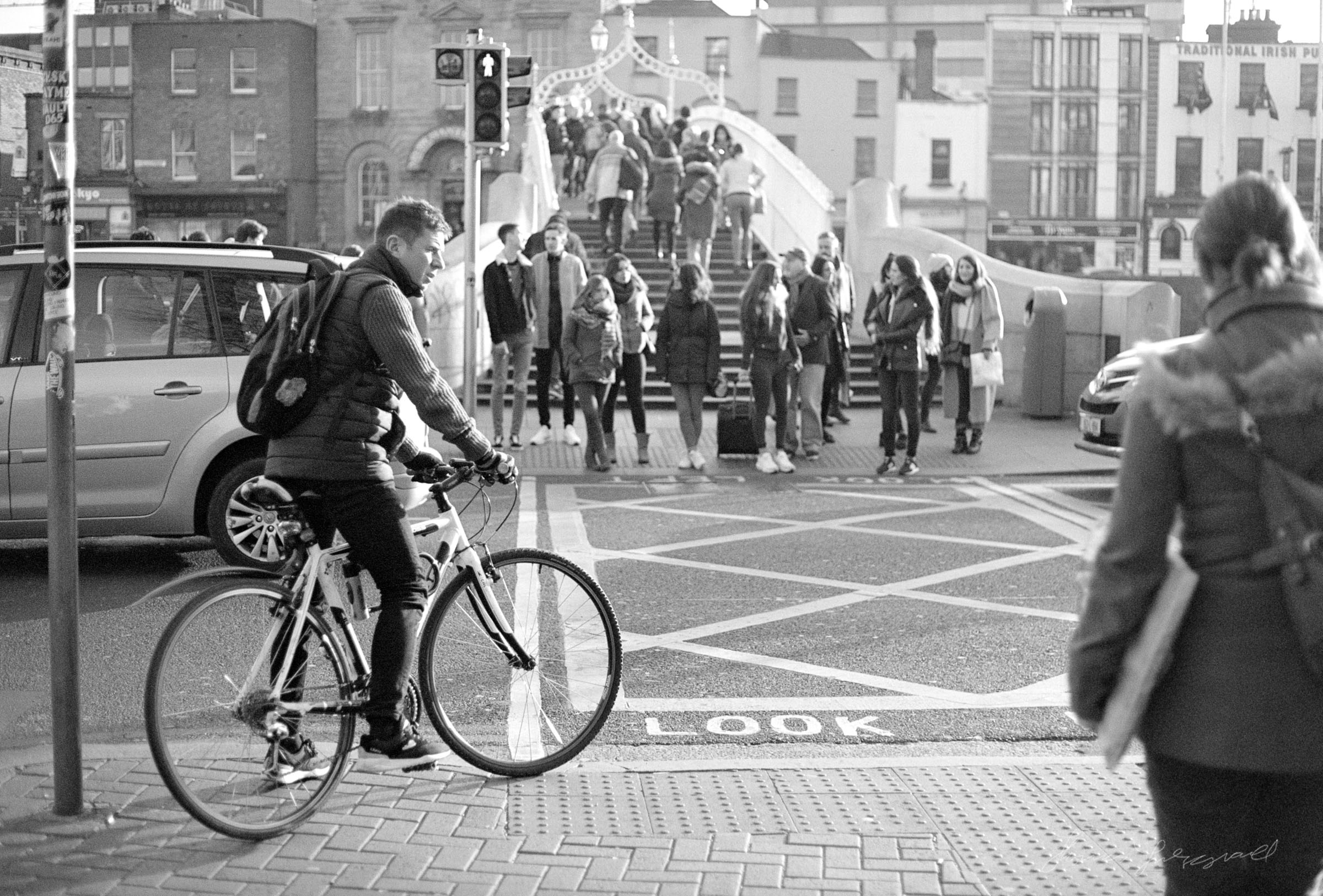 Cyclist waiting to cross at the Ha'Penny Bridge - Streets of Dublin - Dublin on Film