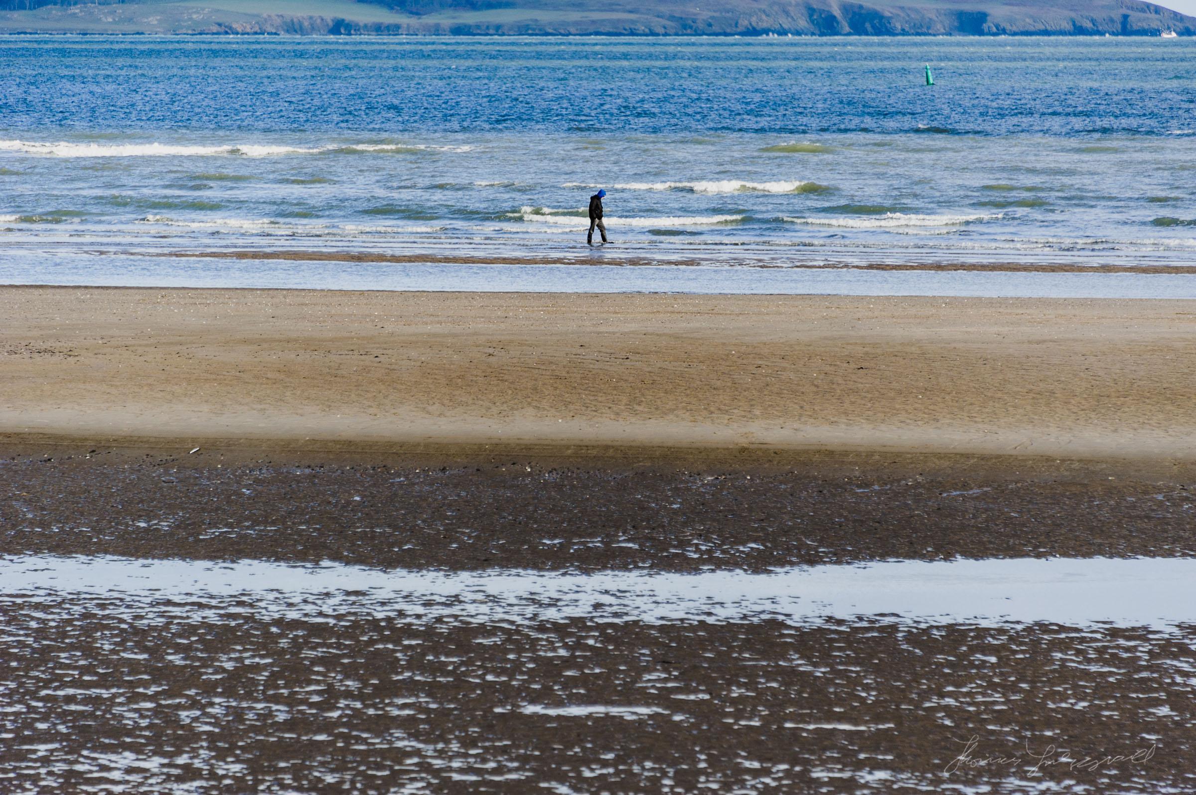 Person walks on the beach at Malahide
