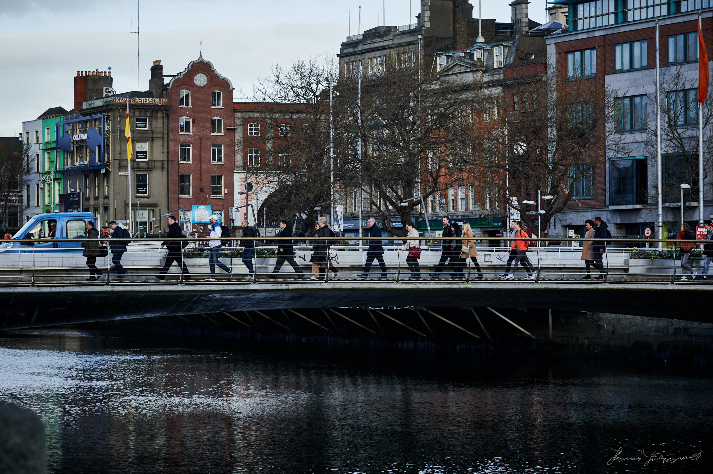 People crossing the Hackett Bridge in the morning on the liffey