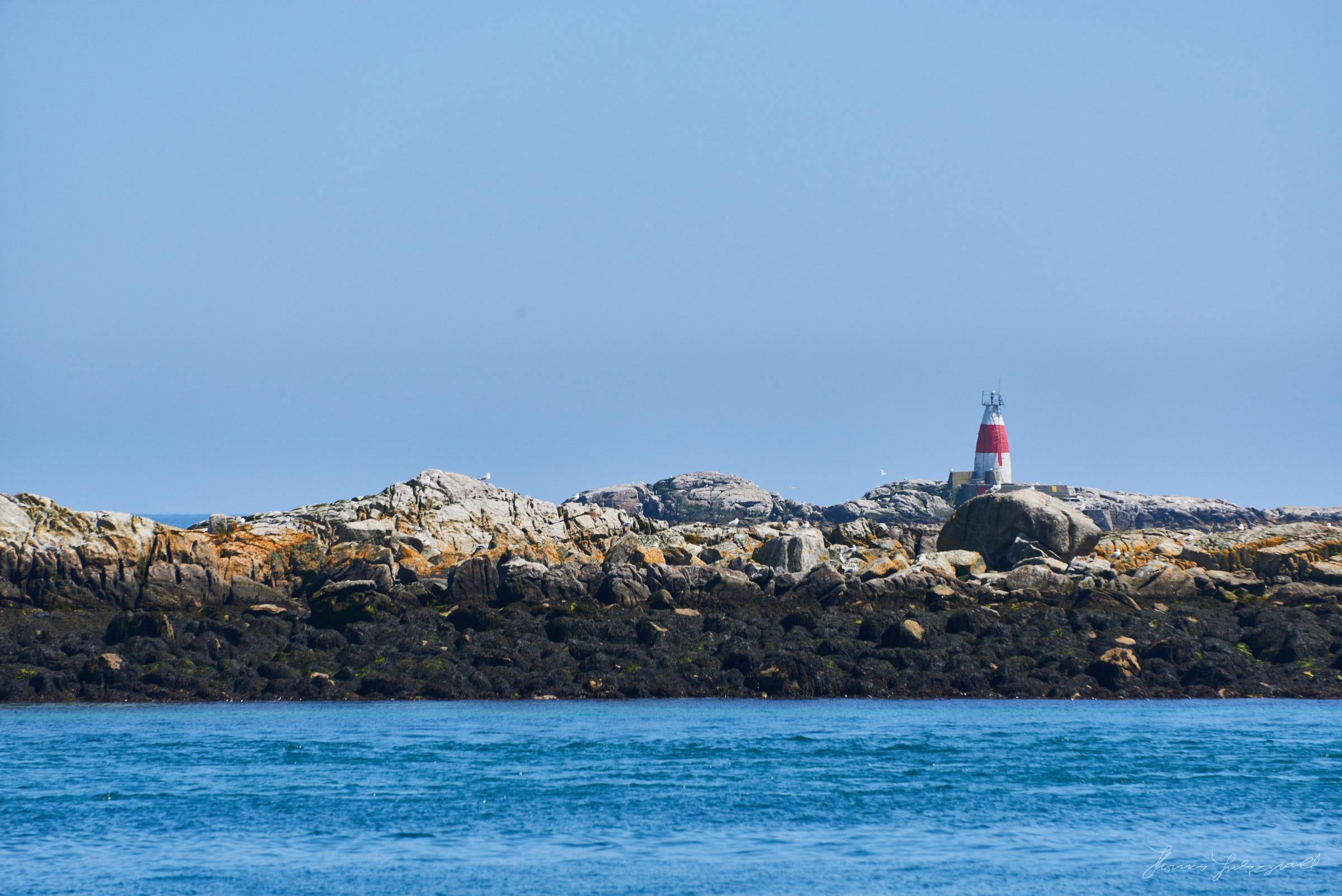Rockey outcrops and sall island formations in Dublin bay, off the cost of Dalkey, with a lightouse or warning buyoy on one of the islands