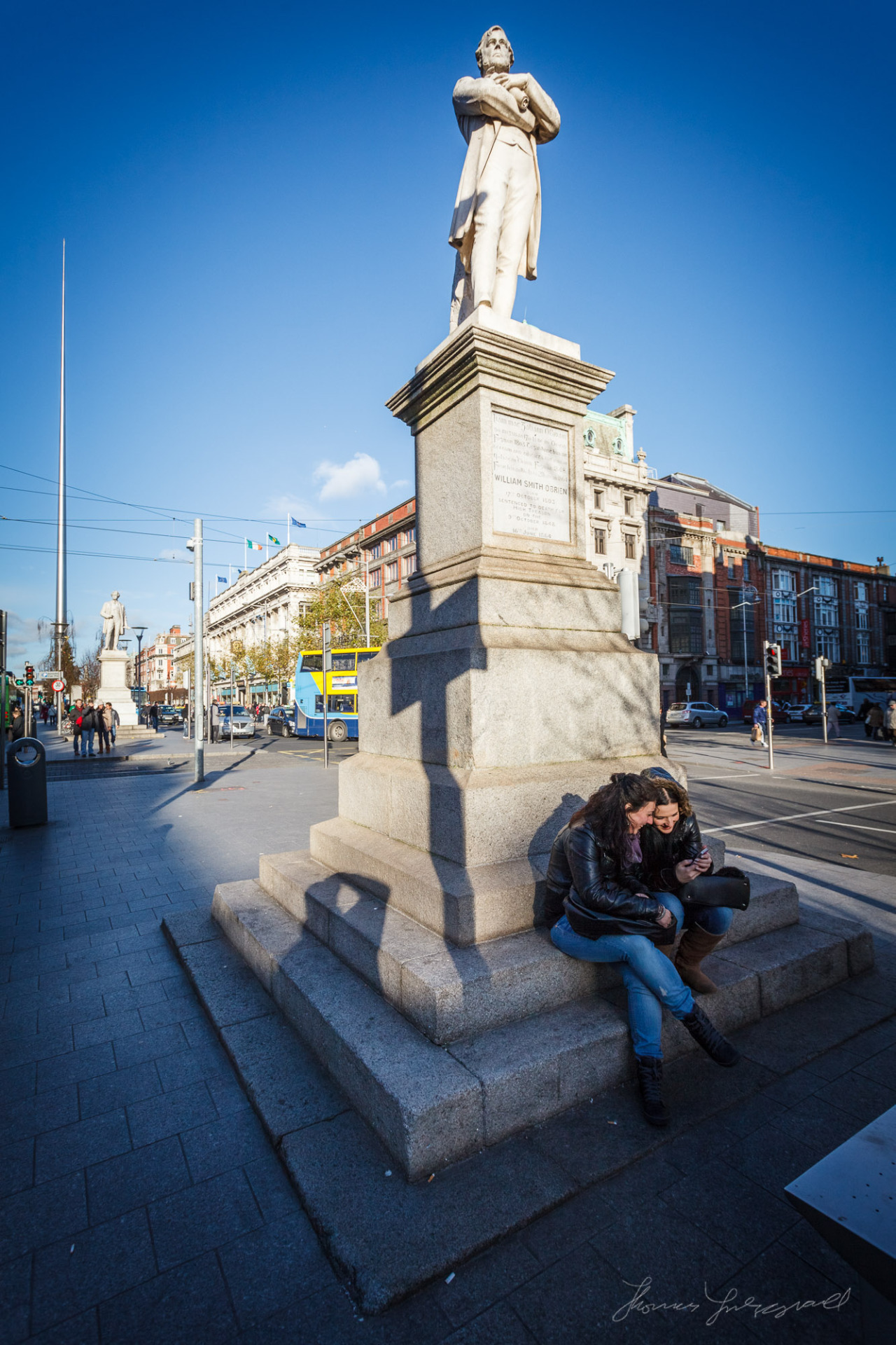 People sitting in front of statue on O'Connell Street