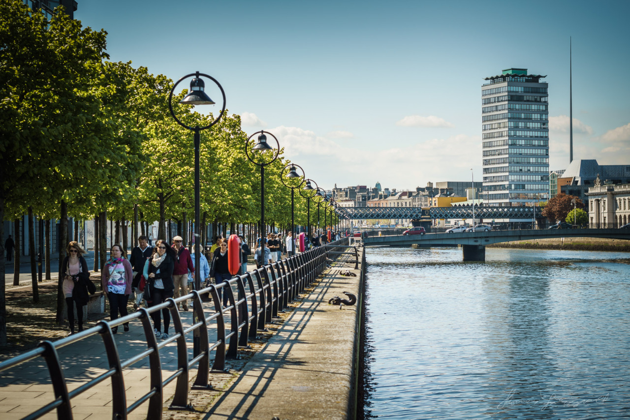 People walking along the Liffey with Liberty Hall in the Background on a sunny Summer's Day last year