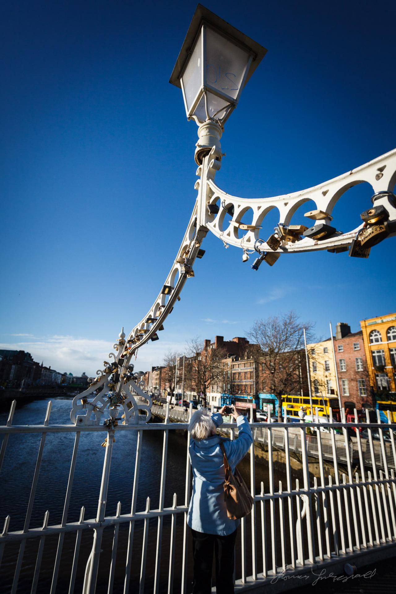 Tourist taking a photograph on the ha'penny bridge in Dublin