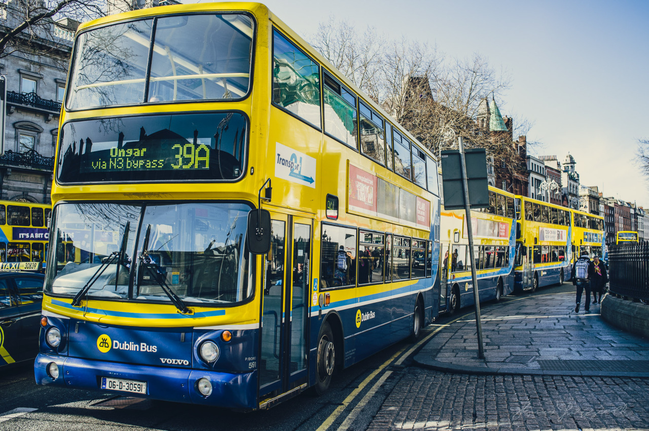 A Line of busses waits at the traffic lights on Dame Street