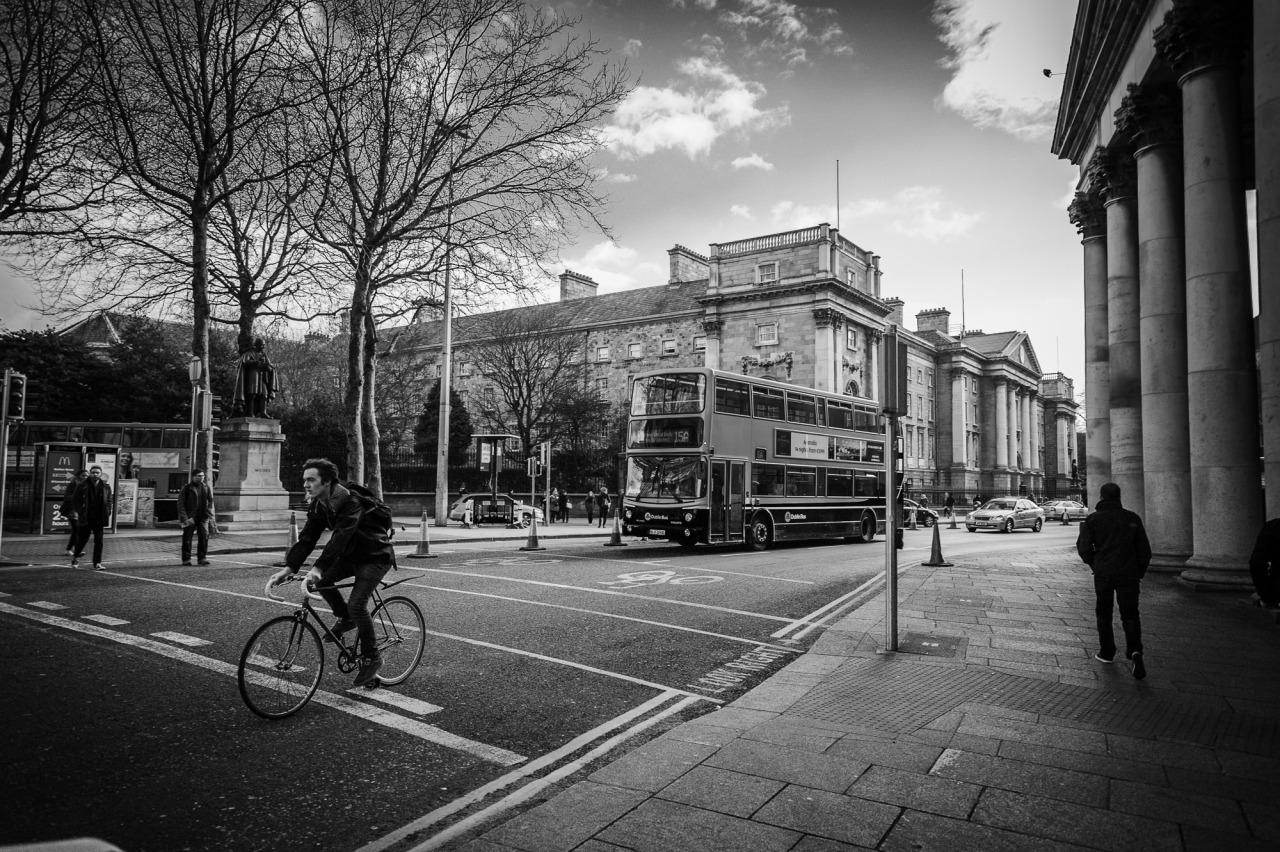 Cycling by College Green and Trinity College
