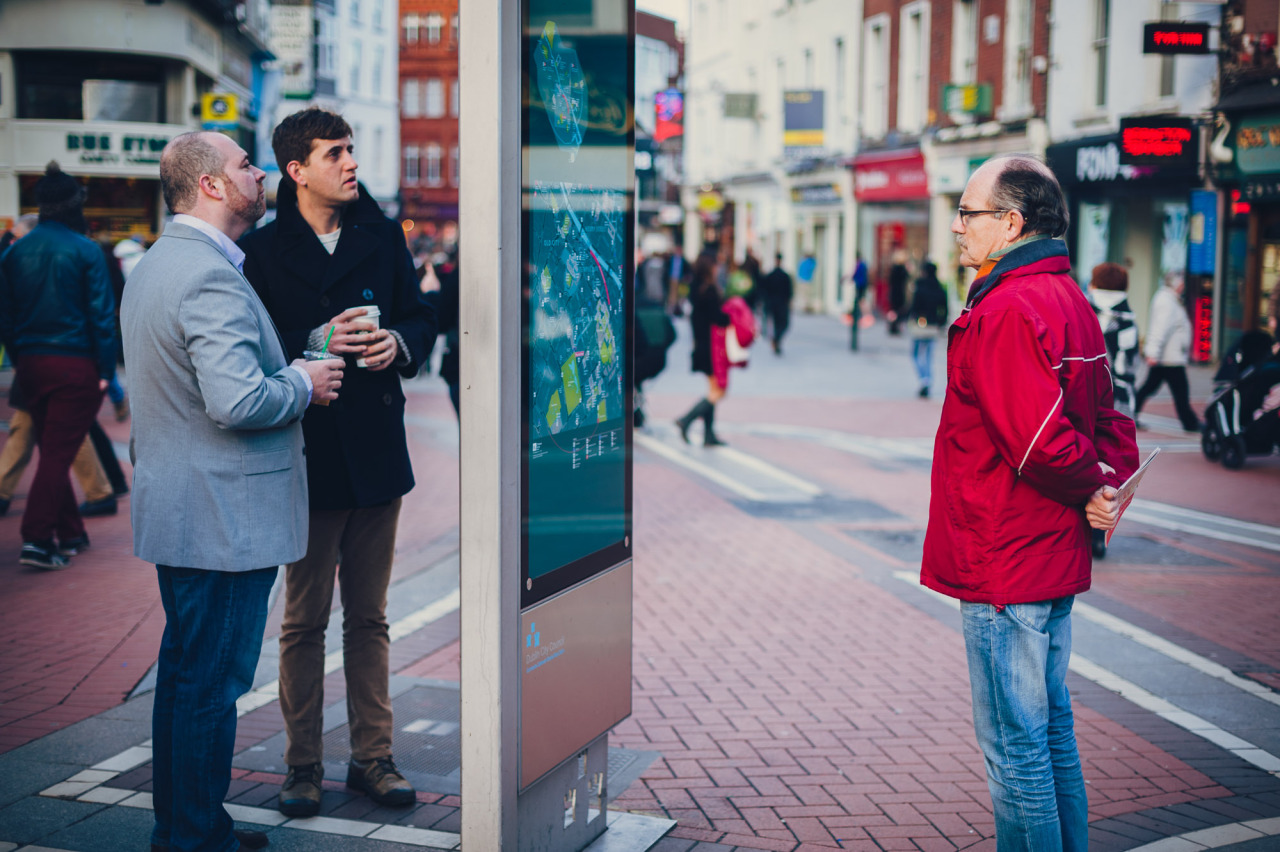 """Looking at the problem from Both Sides""  People examining the map at the top of Grafton Street in Dublin."
