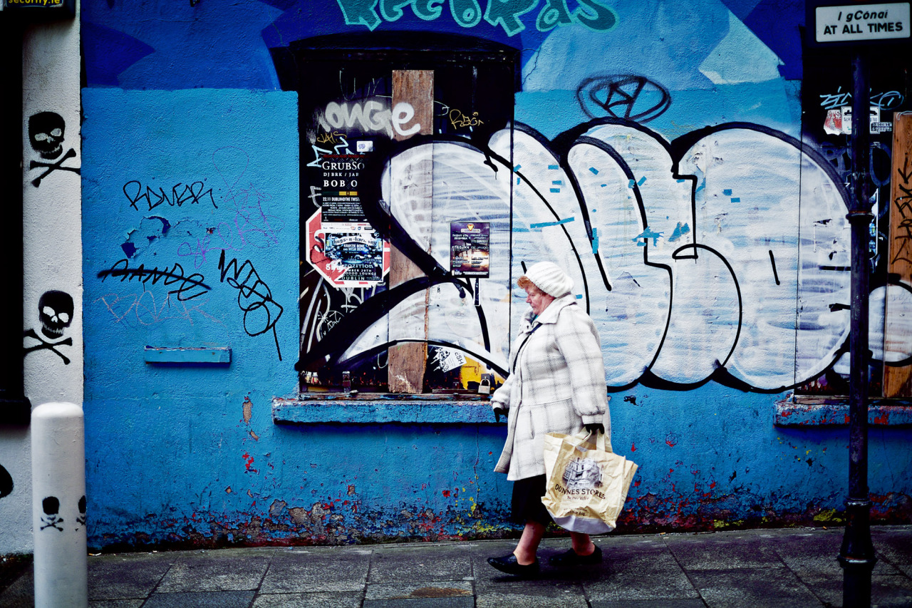"""Woman walking by the graffiti covered walls of the closed """"comet records"""" in Temple Bar, Dublin"""