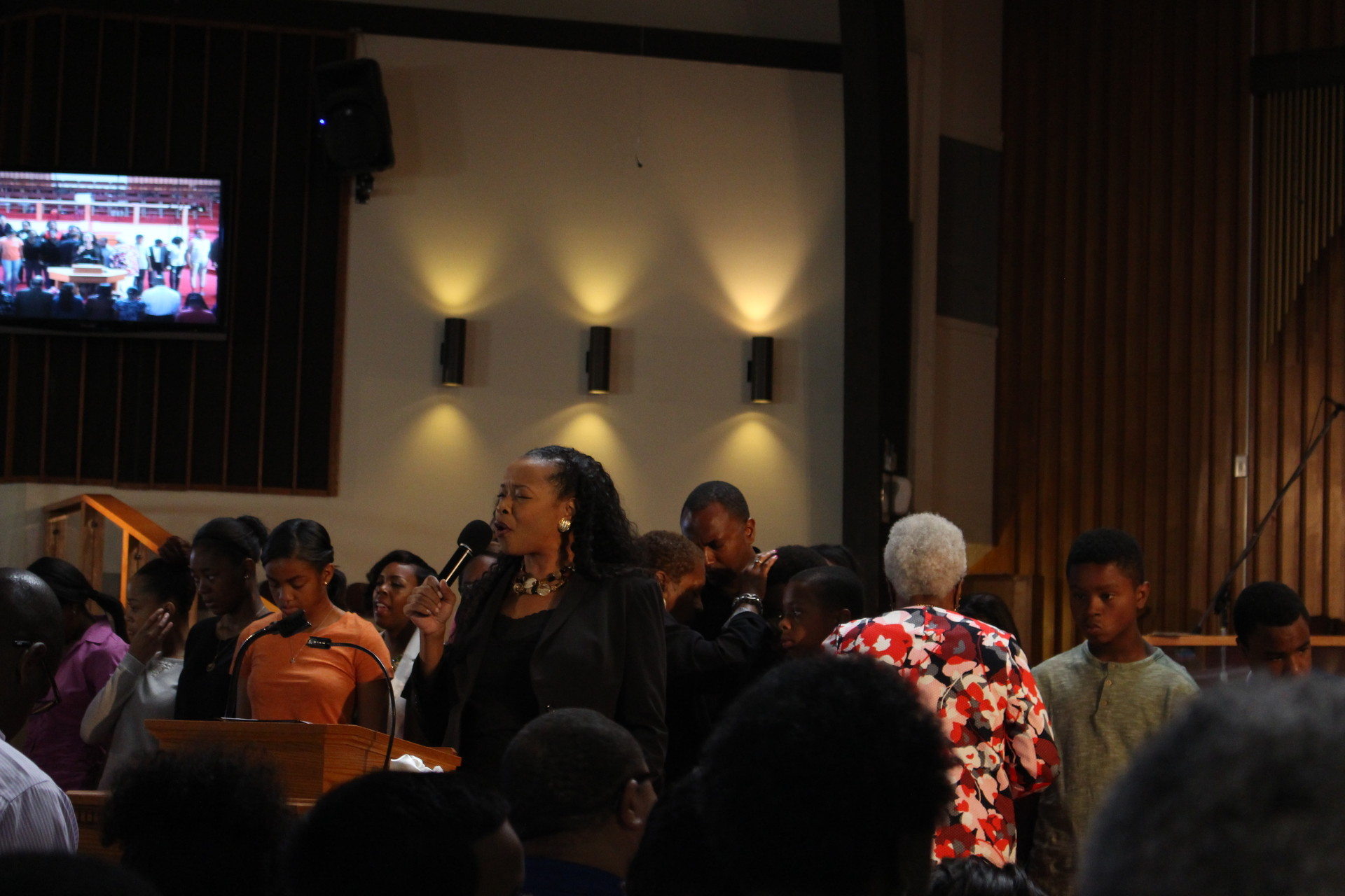 The Rev. Jacqueline Thompson leads prayers at the Allen Temple Baptist Church for those killed during shootings last week by and against police. (Farida Jhabvala Romero/KQED)