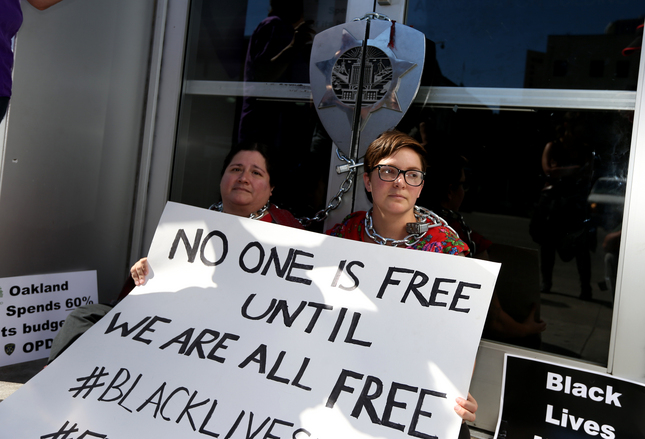 Corazon Amada, left, and Sarah Raridon, both of Oakland, chained themselves to the entrance to the Oakland Police Department along 7th Street in protest against police violence, in Oakland, Calif., on Thursday, July 21, 2016. (Anda Chu/Bay Area News Group)